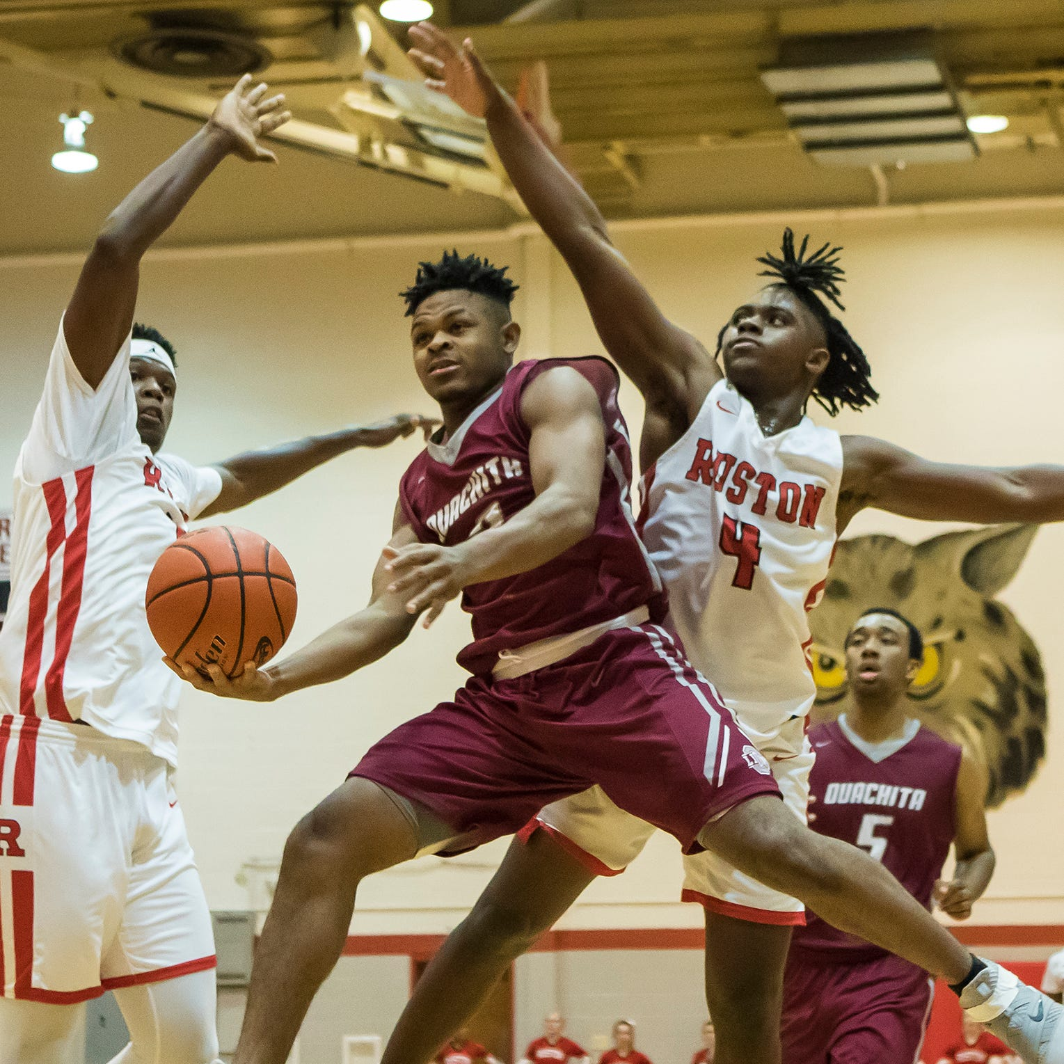 Ouachita's Paul King (2) splits the defending duo of Ruston's Ray Parker (15) and Jordan Williams (4) while going for a lay-up during the game at Ruston High School in Ruston, La. on Feb. 15. Ouachita would win the game 66-49 and complete the regular season undefeated.