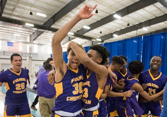 Evangel's Solomon Ayeni (30) and Cordarius Martin (23) celebrate after winning the AISA Class A boys championship game at Cramton Bowl Multiplex in Montgomery, Ala., on Saturday, Feb. 16, 2019. Evangel defeated Chambers 37-34.