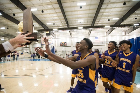 Evangel players run to their trophy after winning the AISA Class A boys championship game at Cramton Bowl Multiplex in Montgomery, Ala., on Saturday, Feb. 16, 2019. Evangel defeated Chambers 37-34.