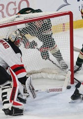 Minnesota Wild's Joel Eriksson Ek, behind the net, scores on a wraparound goal against New Jersey Devils' goalie Keith Kinkaid, left, in the first period of an NHL hockey game Friday, Feb.15, 2019, in St. Paul, Minn.