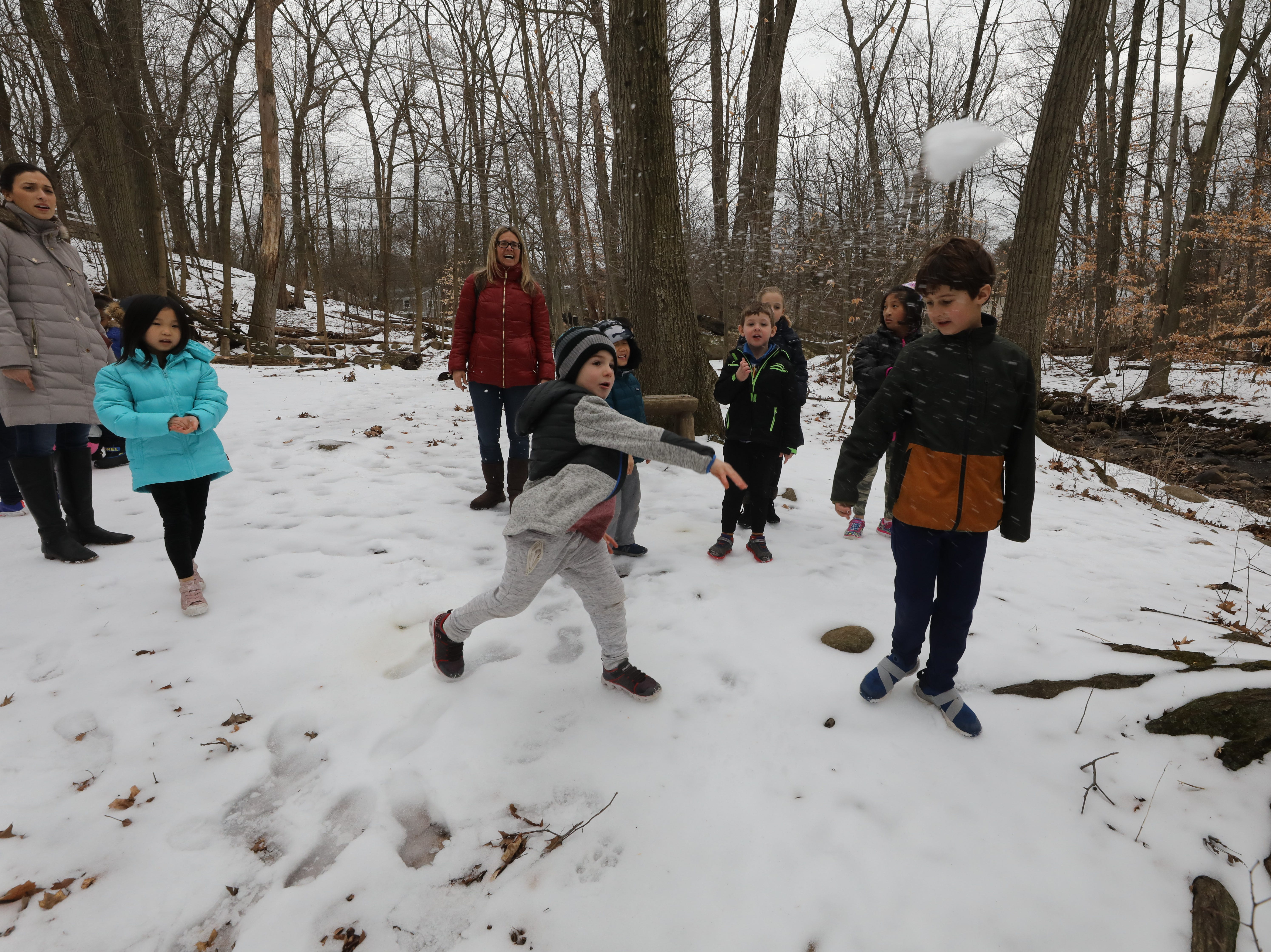 "Kids throwing snowballs into the river as part of a nature walk on February 15, 2019. Ridgewood Parks and Recreation, in partnership with HealthBarn USA, celebrated ""Winterfest"", a day for kids baking cookies, doing yoga and taking a nature walk."