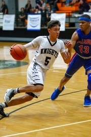 Oñate's Ricky Lujan finds a lane around Bulldawgs forward Ray Brown during Friday's game at OHS.