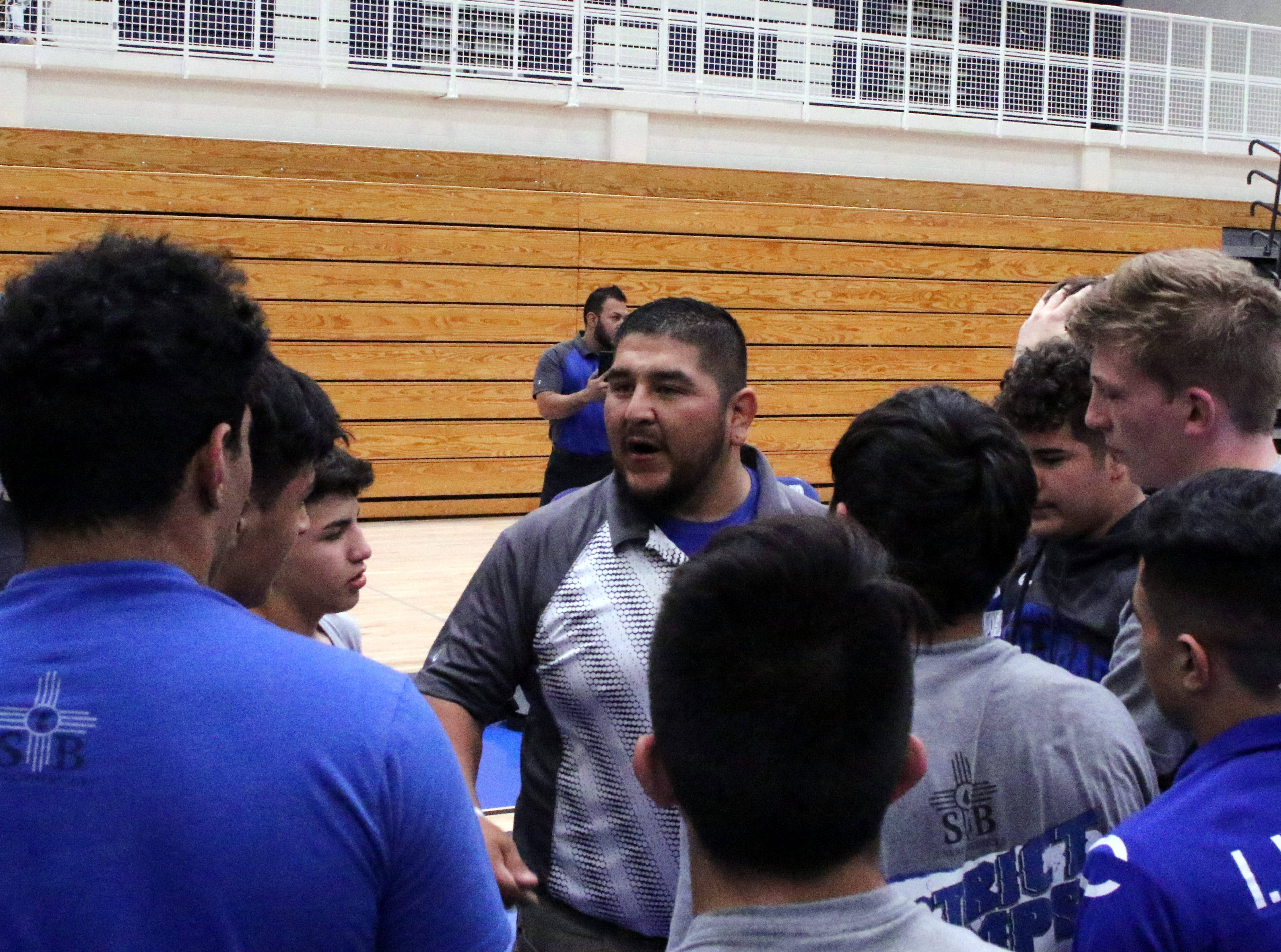 Carlsbad wrestling coach Ryan Salcido talks to his wrestlers before Saturday's tournament begins.