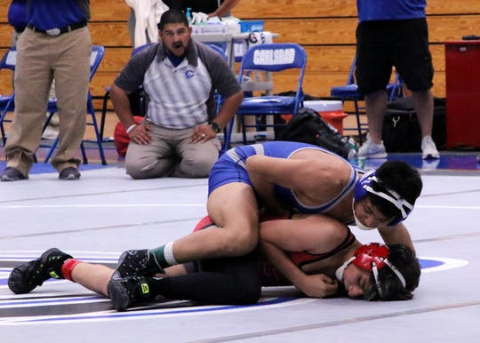 Anthony Fuentes (top) wrestles Kelvin Alarcon of Roswell in the 120-pound division.