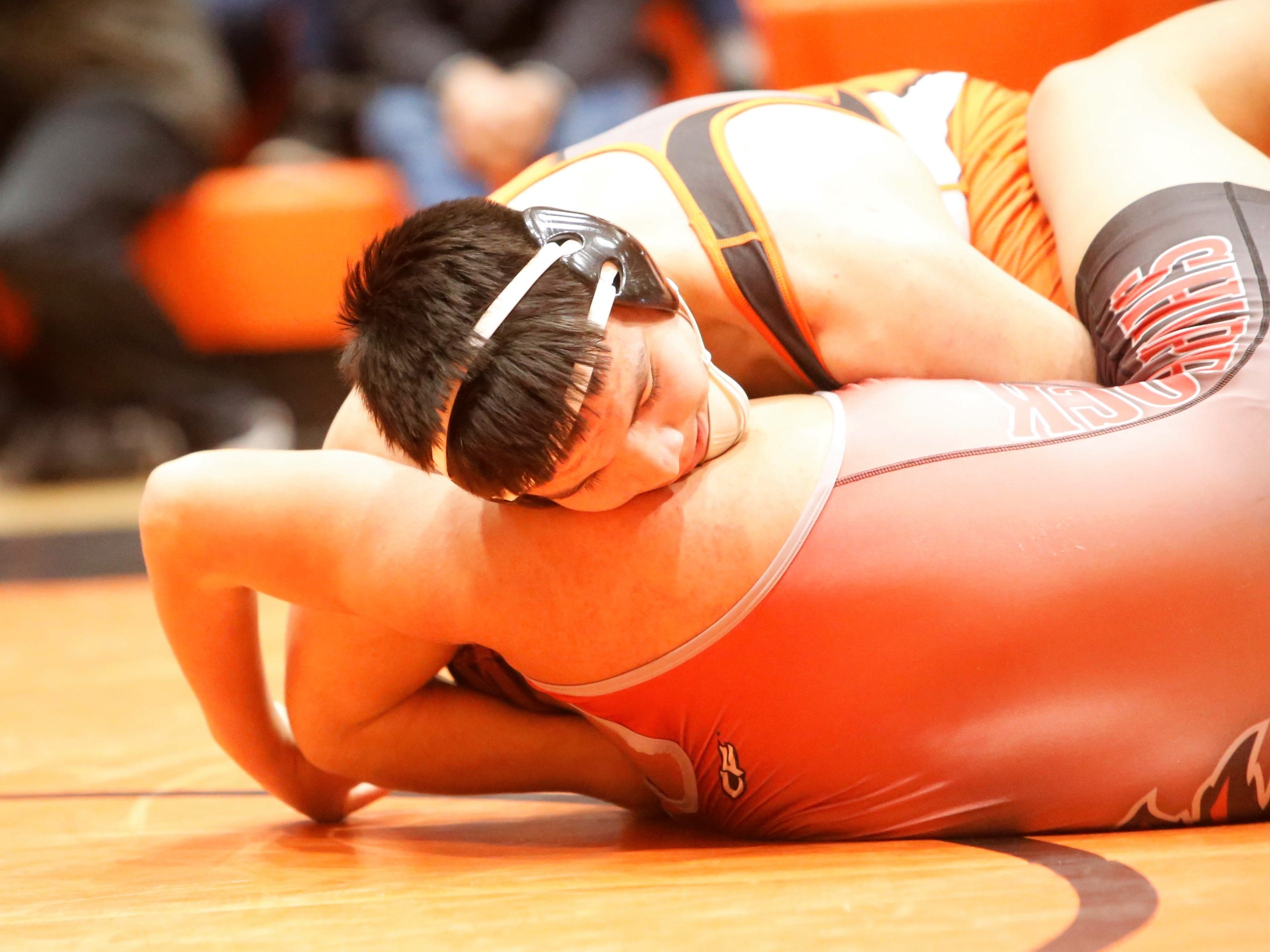 Aztec's Caleb Varzeas grabs hold of Shiprock's Jaylon Begay in a 195-pound division match during the District 1-4A wrestling championships at Lillywhite Gym in Aztec. Varzeas took second place in his division.