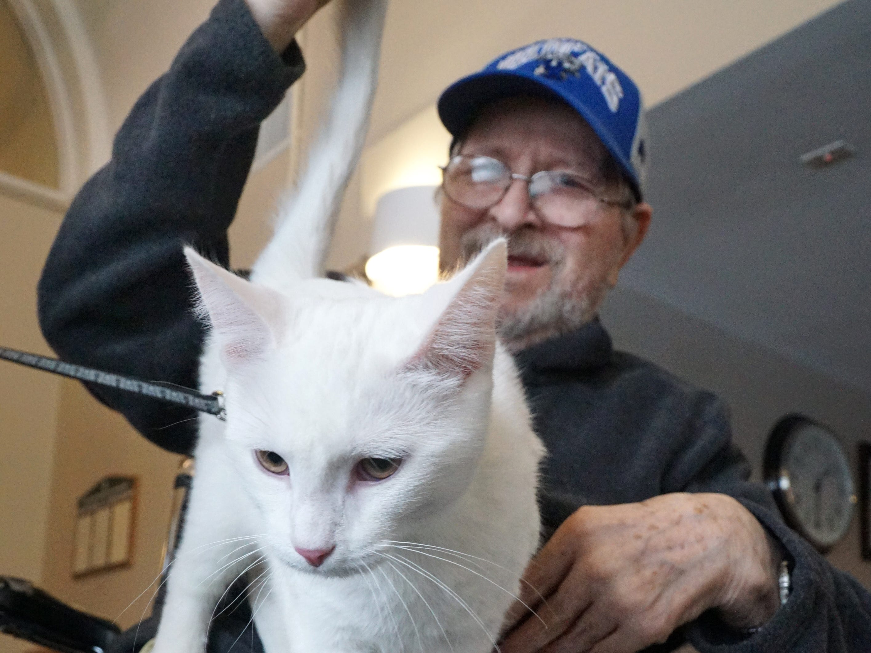 South Lyon Senior Care and Rehab resident John Finkbiner pets a cat at the facility on Feb. 16.