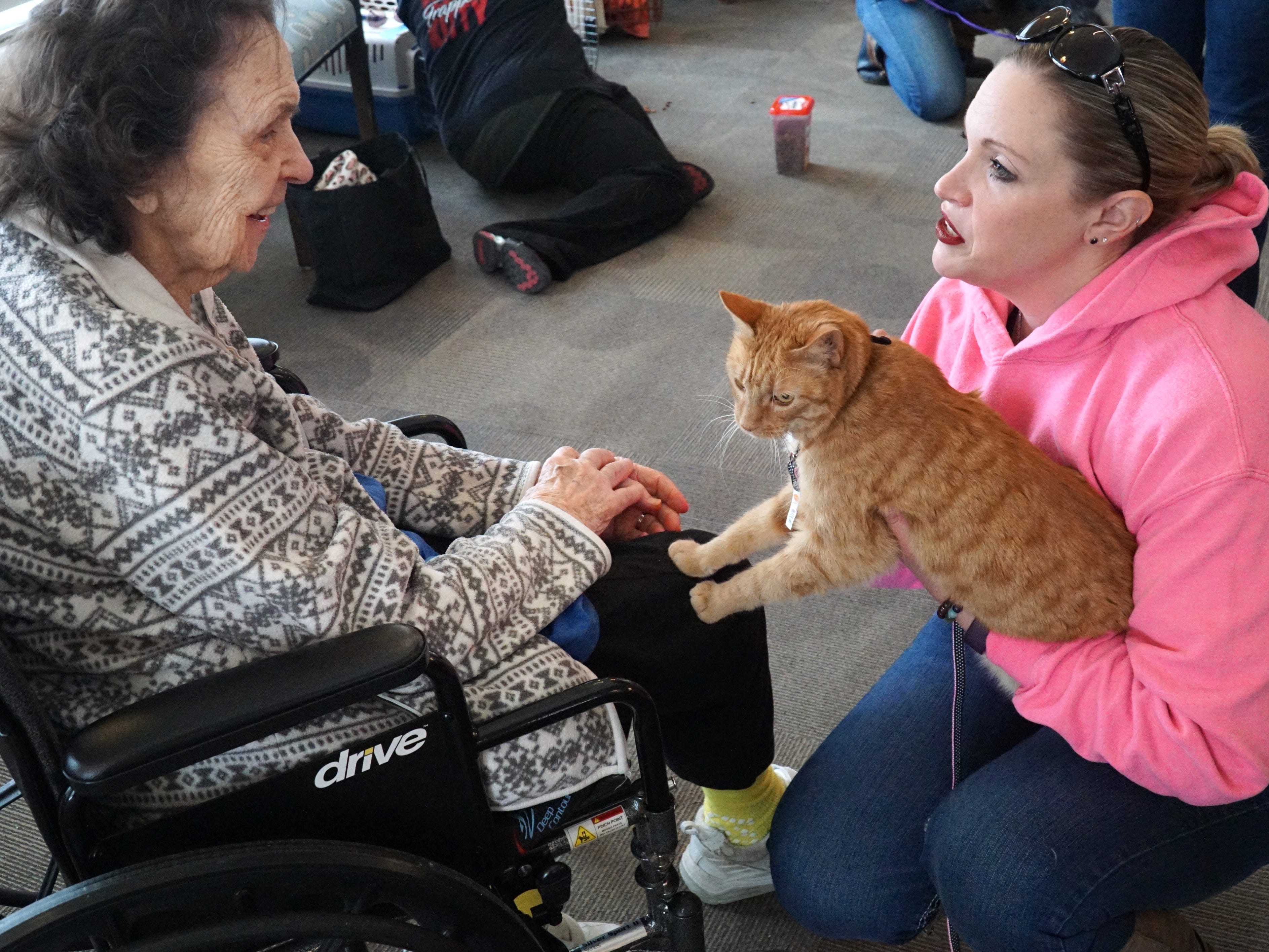Feral Kitty Trapper volunteer Anise Corcoran, right, holds Jolene for South Lyon Senior Care and Rehab resident Dorothy Swan during a Feb. 16 visit.