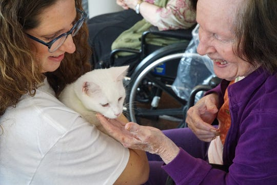 Volunteer Jill Scapelliti holds a white cat up for residednt Yvette Menard to take a look at on Feb. 16.