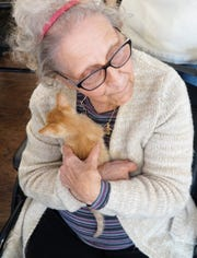 Margie Bernardine holds a kitten during a visit to South Lyon Senior Care and Rehab by Feral Kitty Trappers.