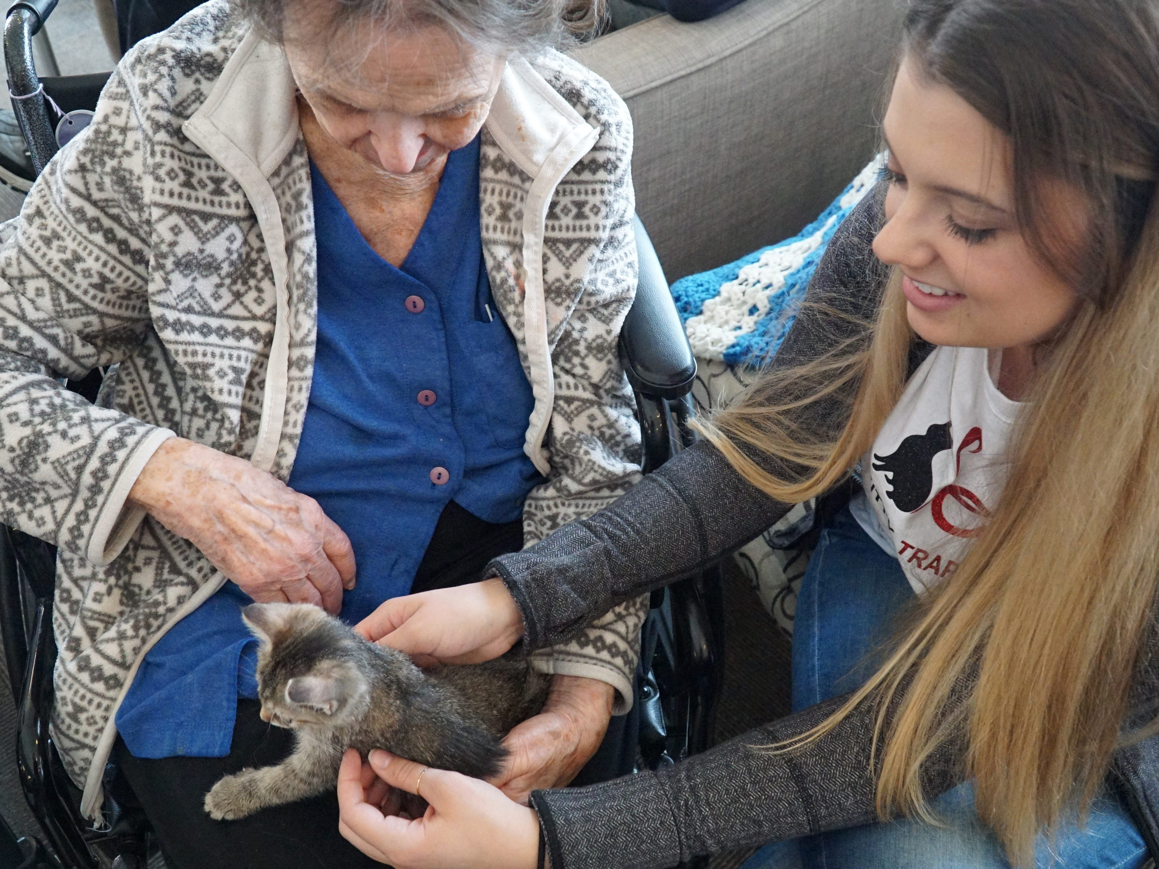 Feral Kitty Trappers volunteer Cailin Gallagher introduces a kitten to a resident.
