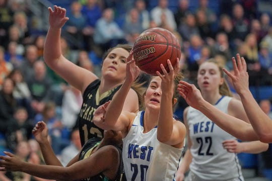 Mia Schlotthauer (20) of Oshkosh West pulls in a rebound against Oshkosh North on Friday.