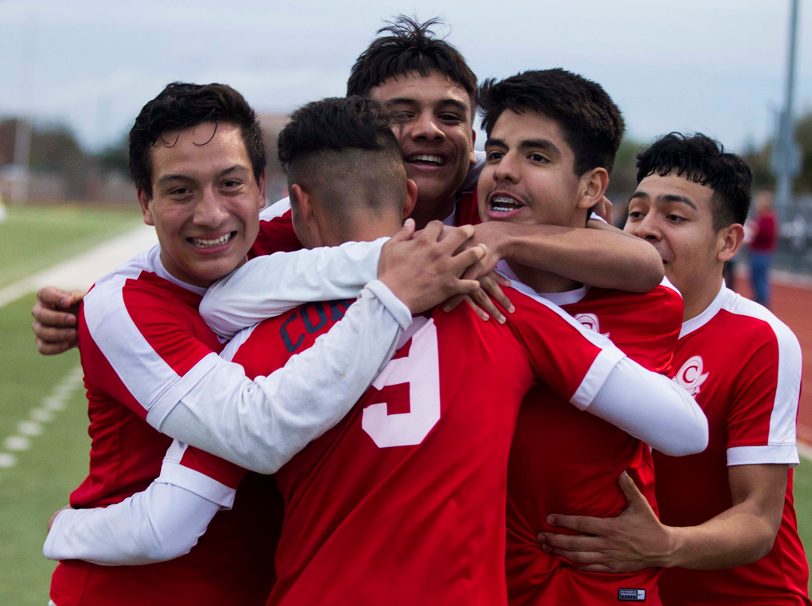 Coronado players hug Gabriel Gonzalez (9) after scoring their second goal during the 3A State Championship game  against Northwest Christian in Chandler, Friday, Feb .15,  2019.