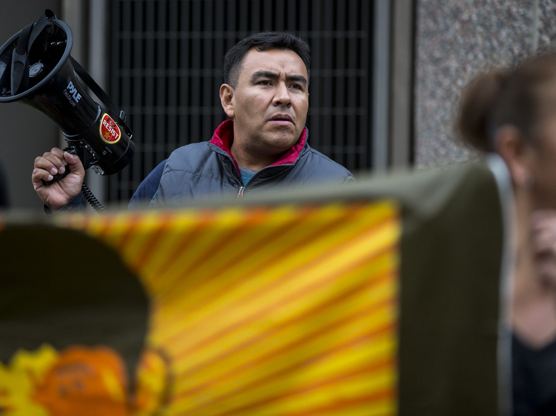 Juan Miguel Cornejo, 42, plays Spanish music through a megaphone during a rally on the one-month anniversary of the police shooting of 14-year-old Antonio Arce on Friday, Feb. 15, 2019, outside Tempe Police headquarters in Tempe, Ariz.