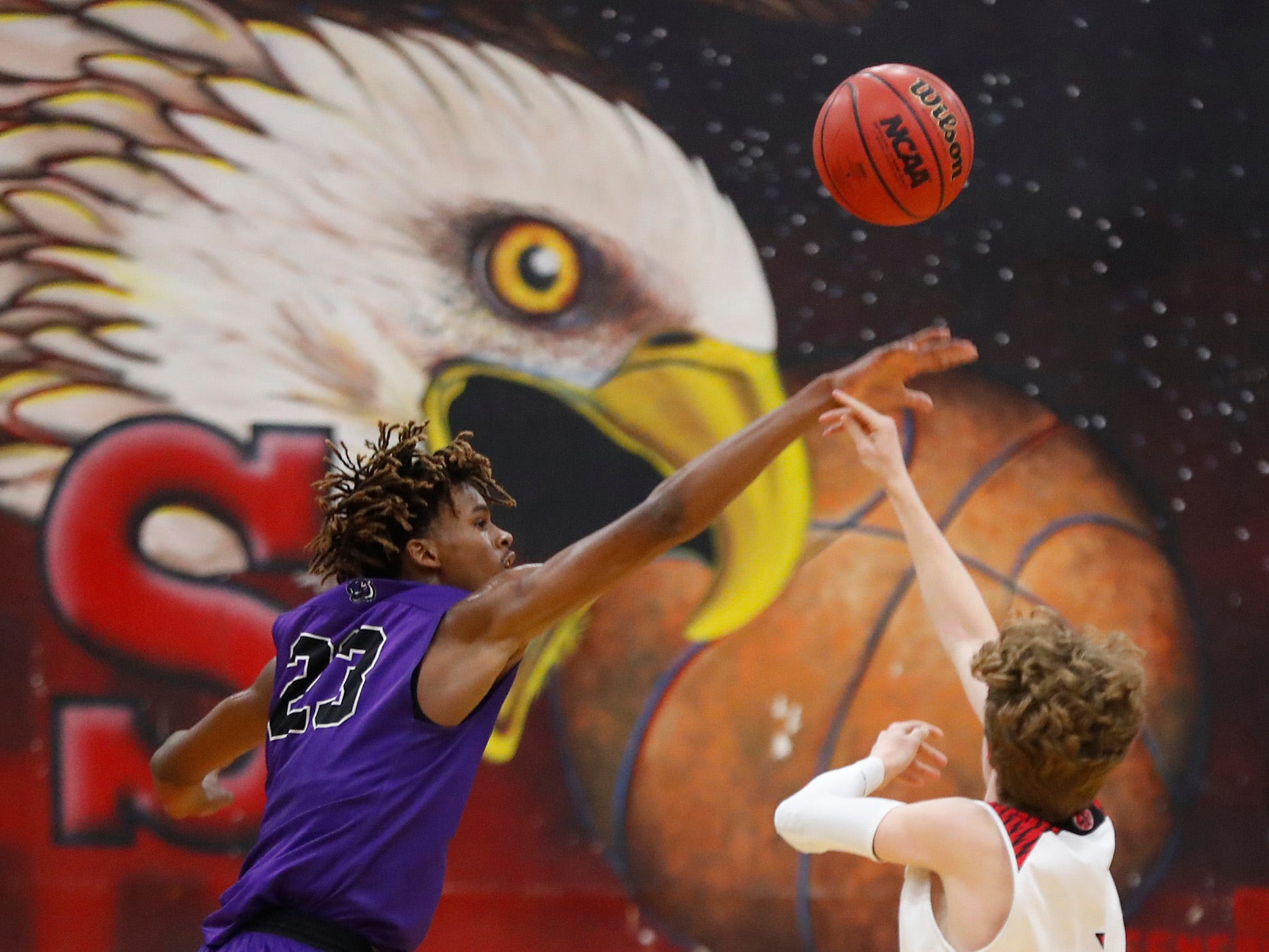 Millennium's DaRon Holmes (23) blocks a shot from Ironwood's Aaron Rice (3) during the first half of the 5A state quarterfinal game at Ironwood High School in Glendale, Ariz. on February 15, 2019.
