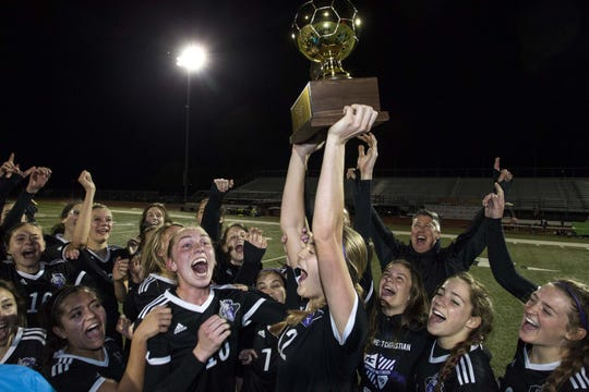 Northwest Christian's Logan Maszton'sÊholds up the gold ball as her team celebrates after winning in overtime the 3A State Championship against Anthem Prep in Chandler, Friday, Feb .15, 2019. Northwest Christian won 1-0 in overtime.