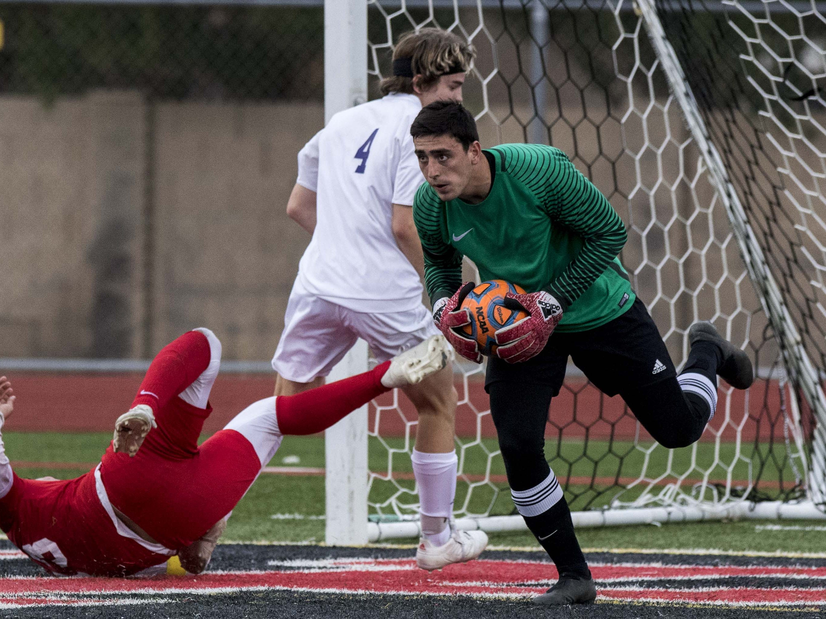 Northwest Christian goalie Ben Ogan (0) cradles the ball as  Coronado's Adan Valle (13) gets tied up with Northwest Christian's Levi Delapiedra (4) during the 3A State Championship game in Chandler, Friday, Feb .15,  2019.