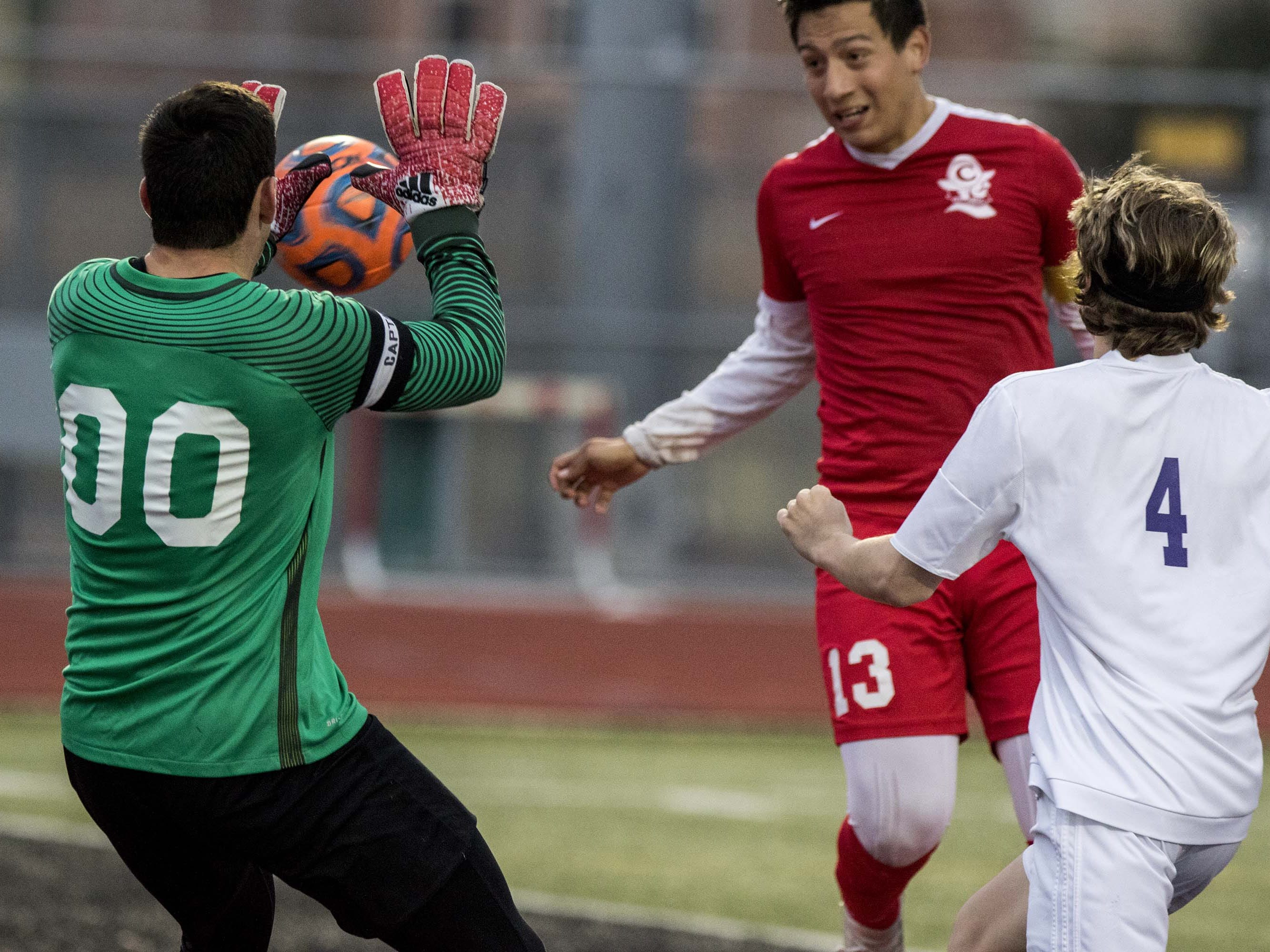 Northwest Christian goalie Ben Ogan (0) couldn't get to the head ball from Coronado's Adan Valle (13) as Valle's scores the Dons' first goal during the 3A State Championship game in Chandler, Friday, Feb .15,  2019.
