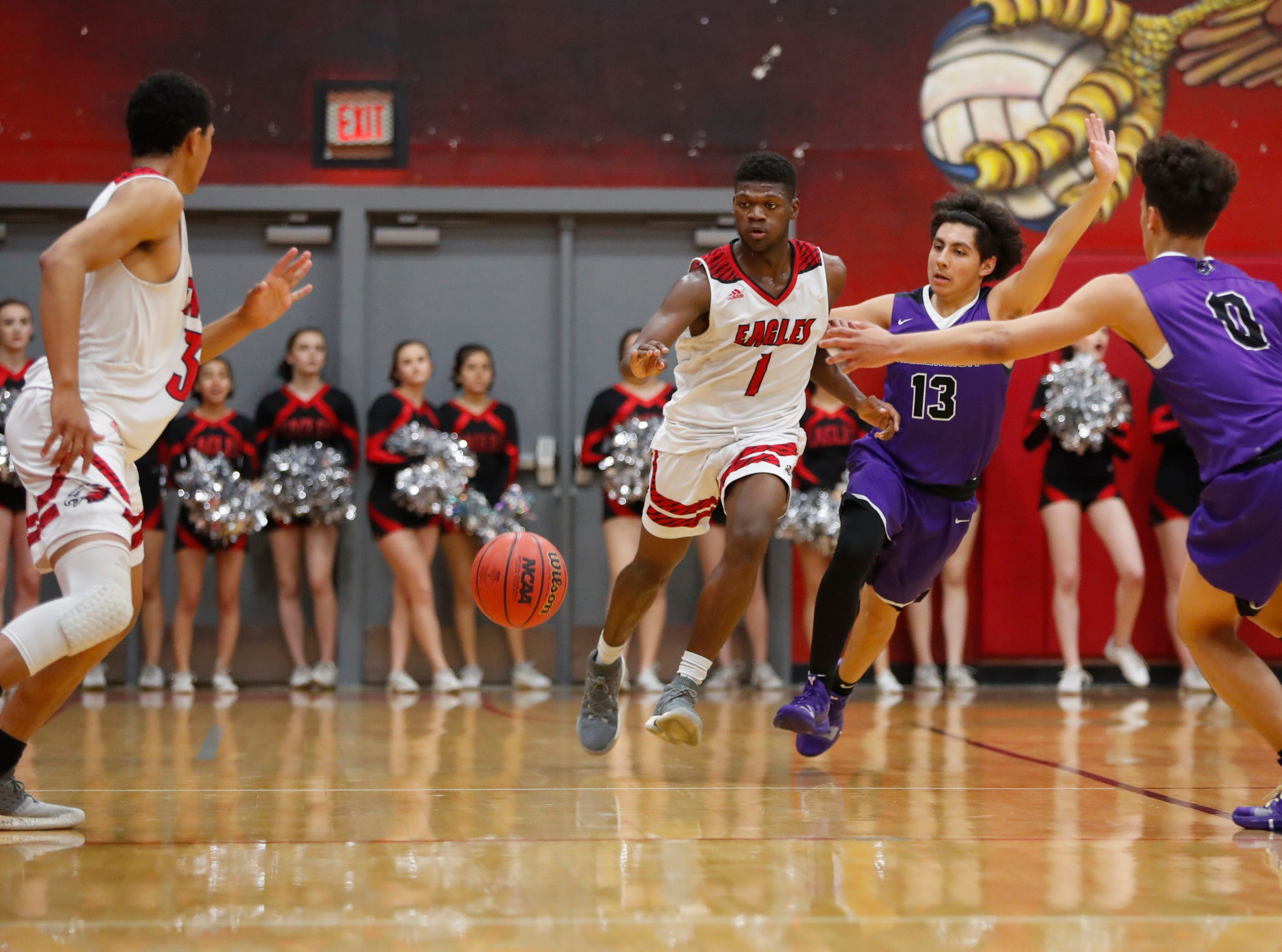 Ironwood's Malik Smith (1) makes a pass under pressure from Millennium's Jose Cortes (13) during the second half of the 5A state quarterfinal game at Ironwood High School in Glendale, Ariz. on February 15, 2019.