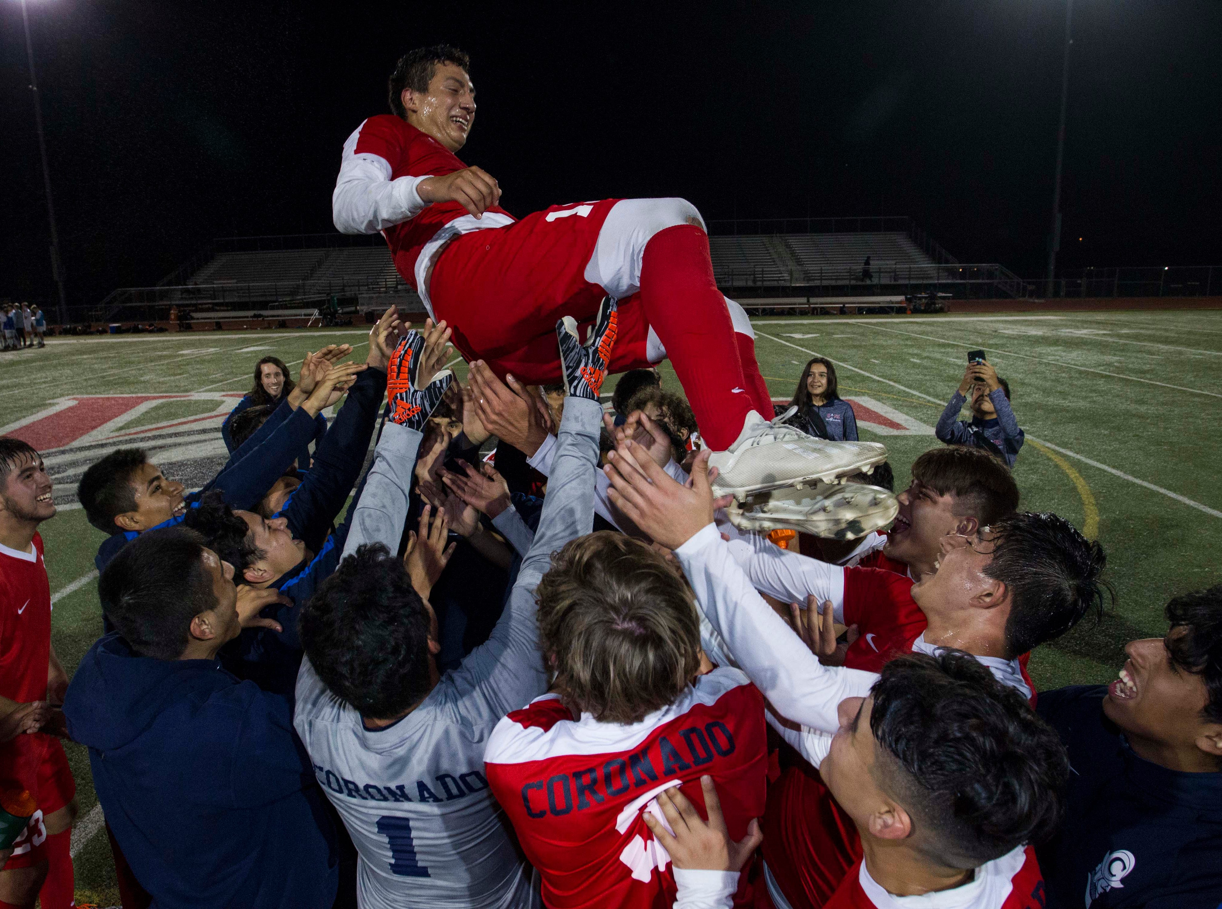 Coronado players throw Adan Valle (13) into the air after their 5-0 win over Northwest Christian in the 3A State Championship game  against  in Chandler, Friday, Feb .15,  2019.