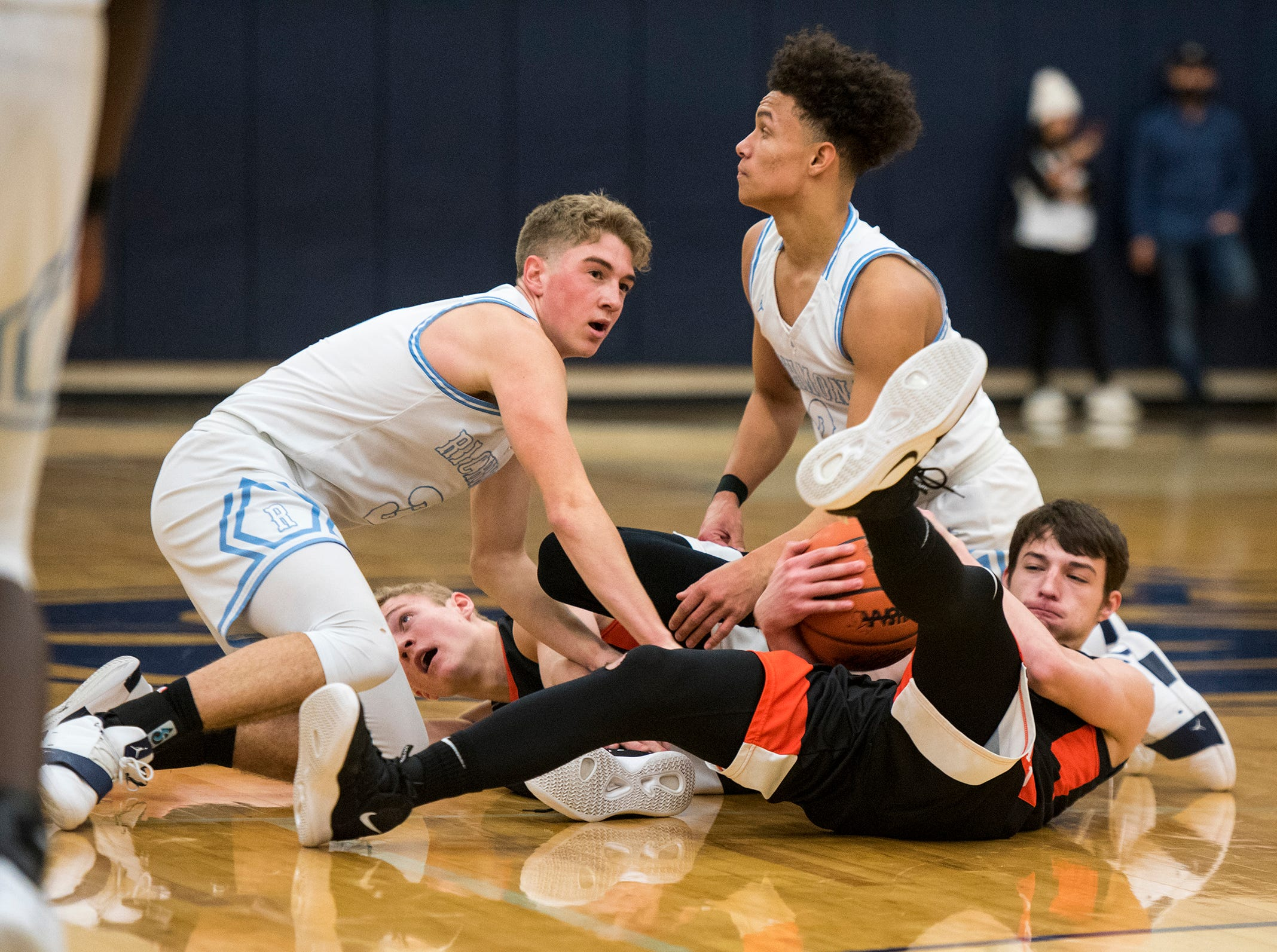 Players fight for the ball during a basketball game between Richmond and Almont High School Friday, Feb. 15, 2019 at Richmond High School.