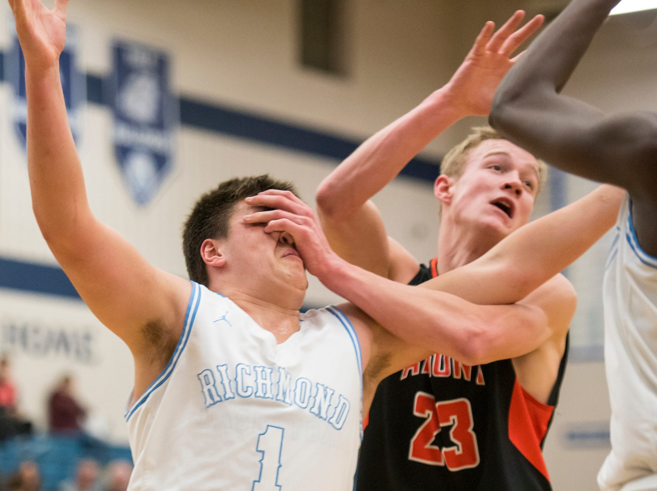 Almont High School forward Colby Schapman (23) pushes against Richmond's Connor Cracchiolo while they fight for a rebound during their basketball game Friday, Feb. 15, 2019 at Richmond High School.