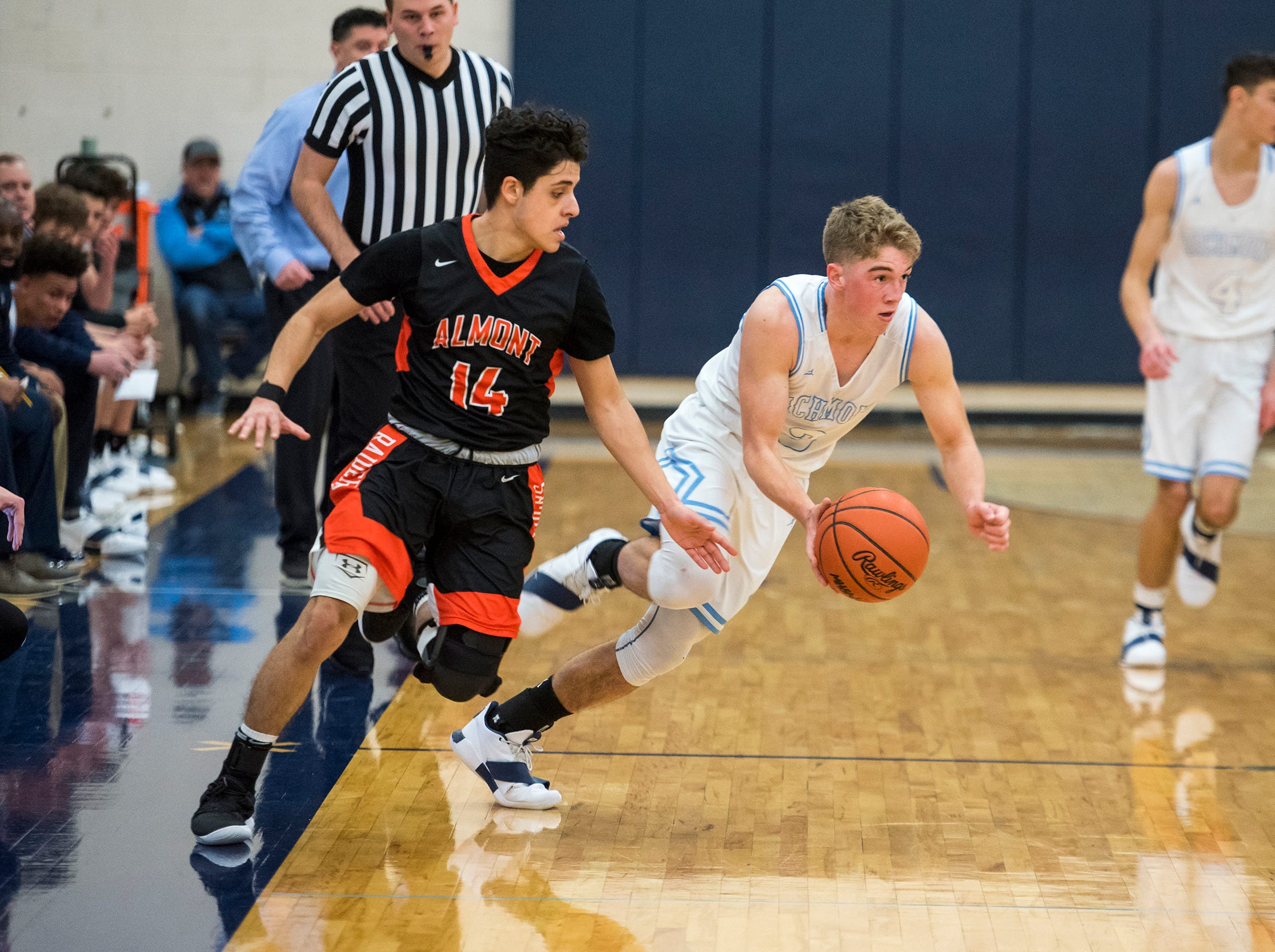 Richmond guard Jackson Allen (right) runs with the ball away from Almont High School guard Rafael Farias after recovering it during their basketball game Friday, Feb. 15, 2019 at Richmond High School.