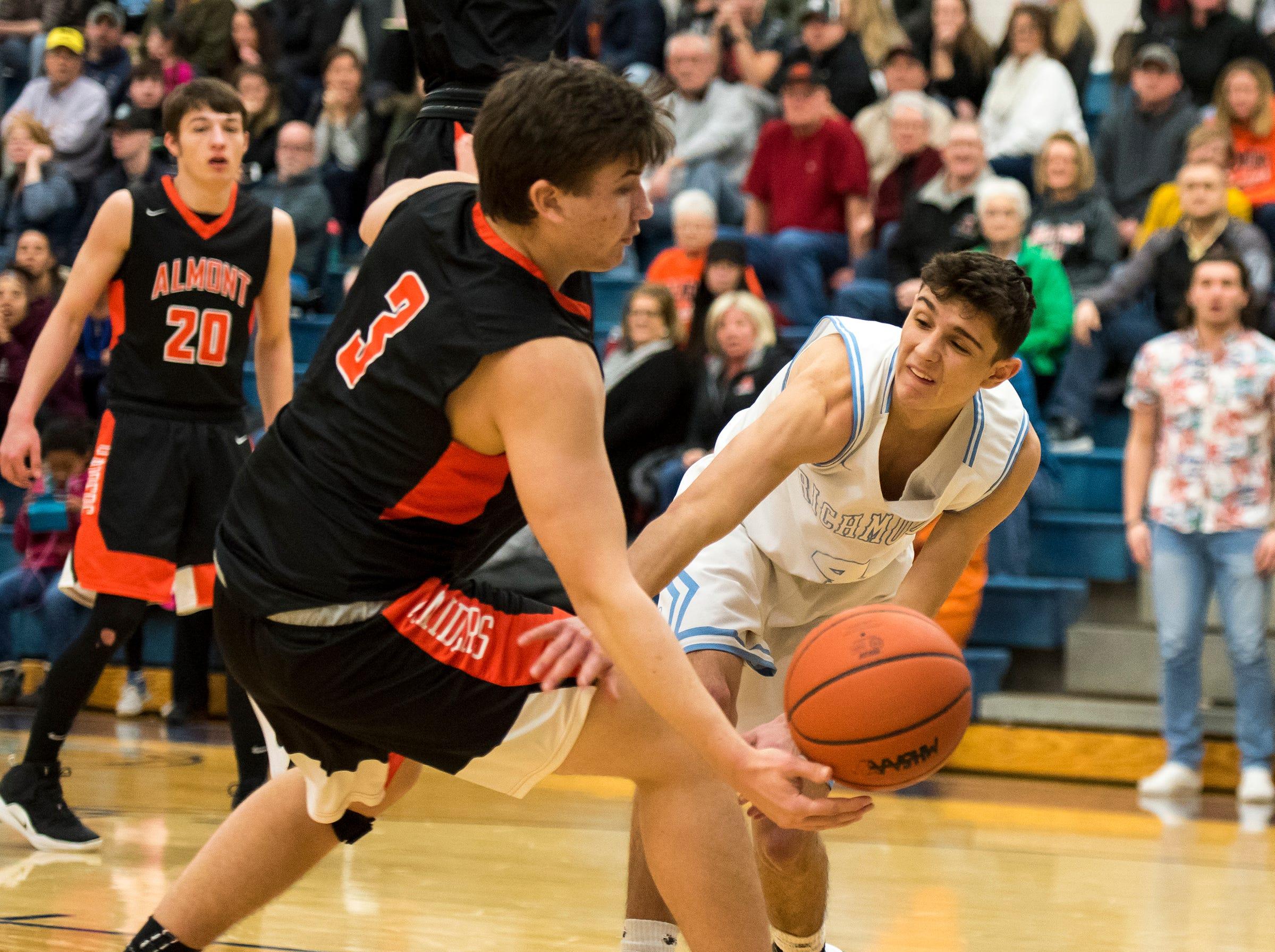 Almont High School guard Gabe Bourdeau (3) blocks a pass by Richmond guard Brandon Schorman during their basketball game Friday, Feb. 15, 2019 at Richmond High School.
