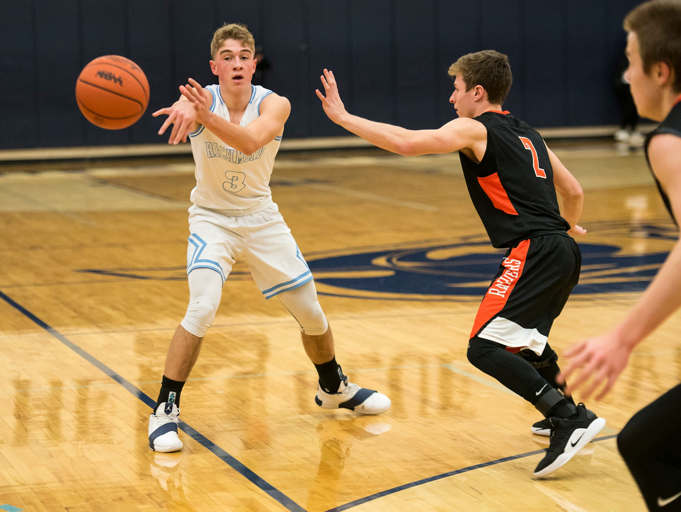 Richmond guard Jackson Allen (3) passes the ball away from Almont High School guard Cameron Asaro during their basketball game Friday, Feb. 15, 2019 at Richmond High School.