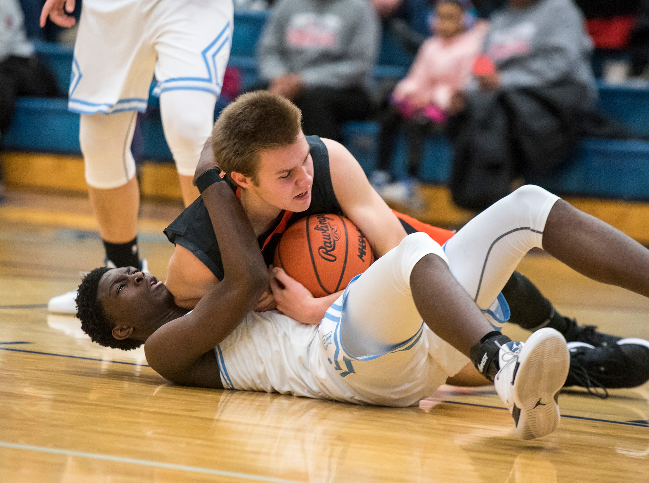 RIchmond guard Daveyon Henderson (bottom) fights with Almont guard Atte Vuoristo for the ball during their basketball game Friday, Feb. 15, 2019 at Richmond High School.