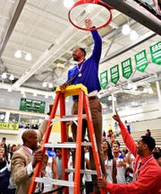 York High head coach Clovis Gallon Sr. holds up the net following the Bearcats' 54-50 win over New Oxford in the York-Adams League boys' basketball championship. Dawn J. Sagert photo