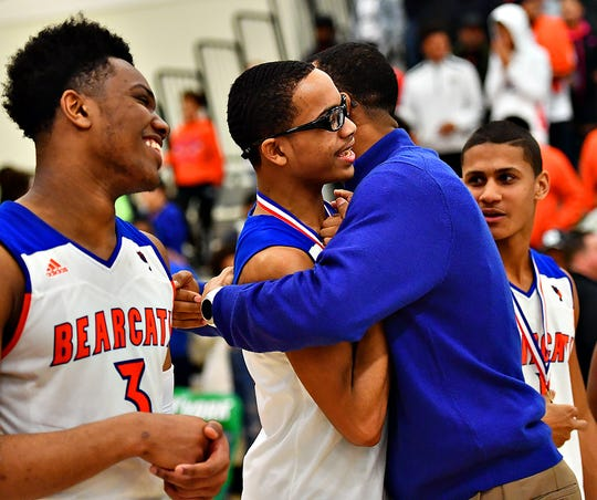 York High head coach Clovis Gallon Sr. hugs his son Cameron Gallon as his oldest son, Clovis Gallon Jr., left, watches after the Bearcats' 54-50 win over New Oxford in the York-Adams League boys' basketball tournament championship. Dawn J. Sagert photo