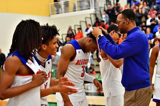 York High head coach Clovis Gallon Sr. puts the gold medal around Clovis Gallon Jr.'s neck. Dawn J. Sagert photo