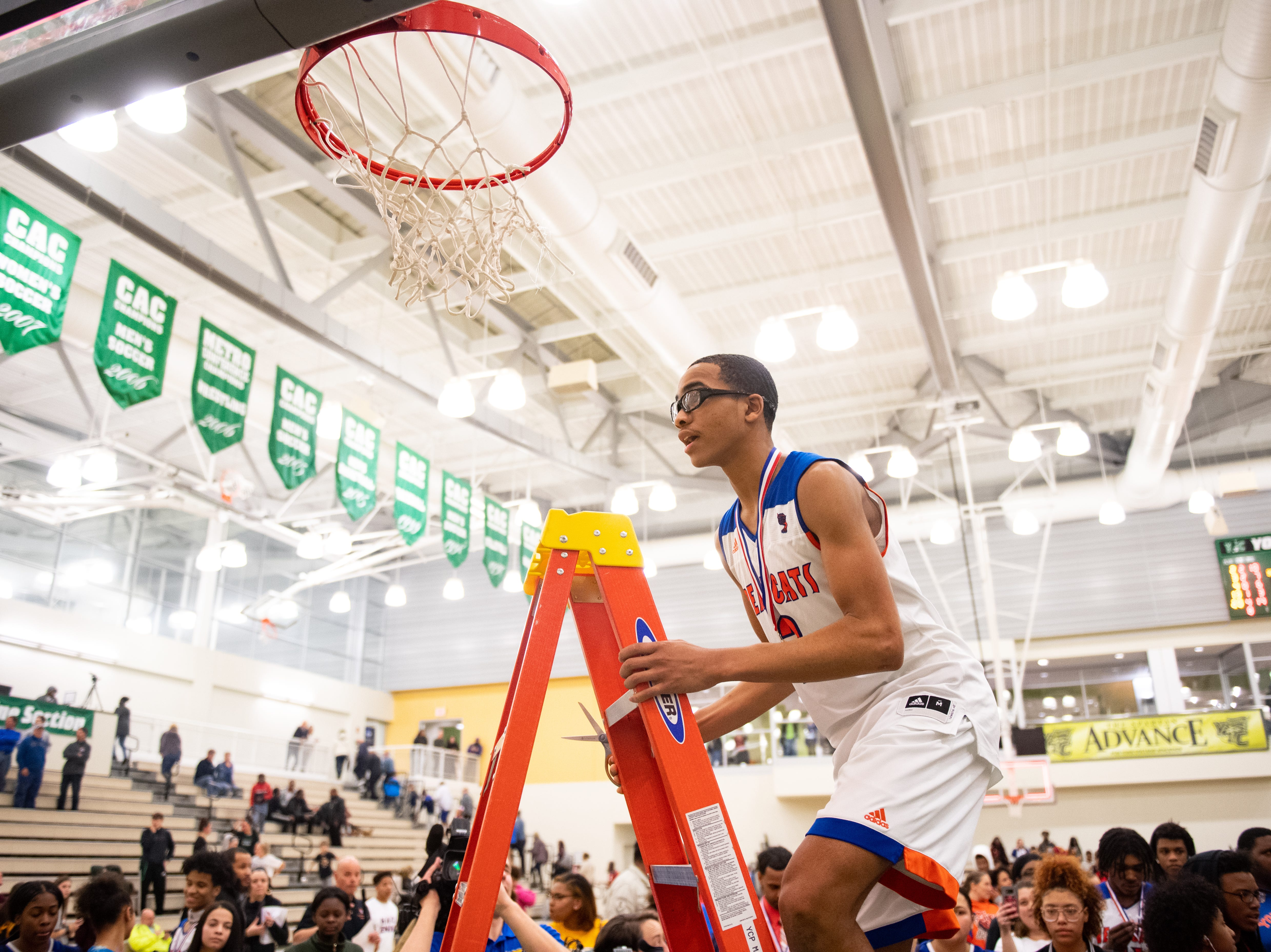 Cameron Gallon climbs up to the net after the YAIAA Division I title game between York High and New Oxford, Friday, February 15, 2019 at York College. The Bearcats defeated the Colonials 54 to 50.