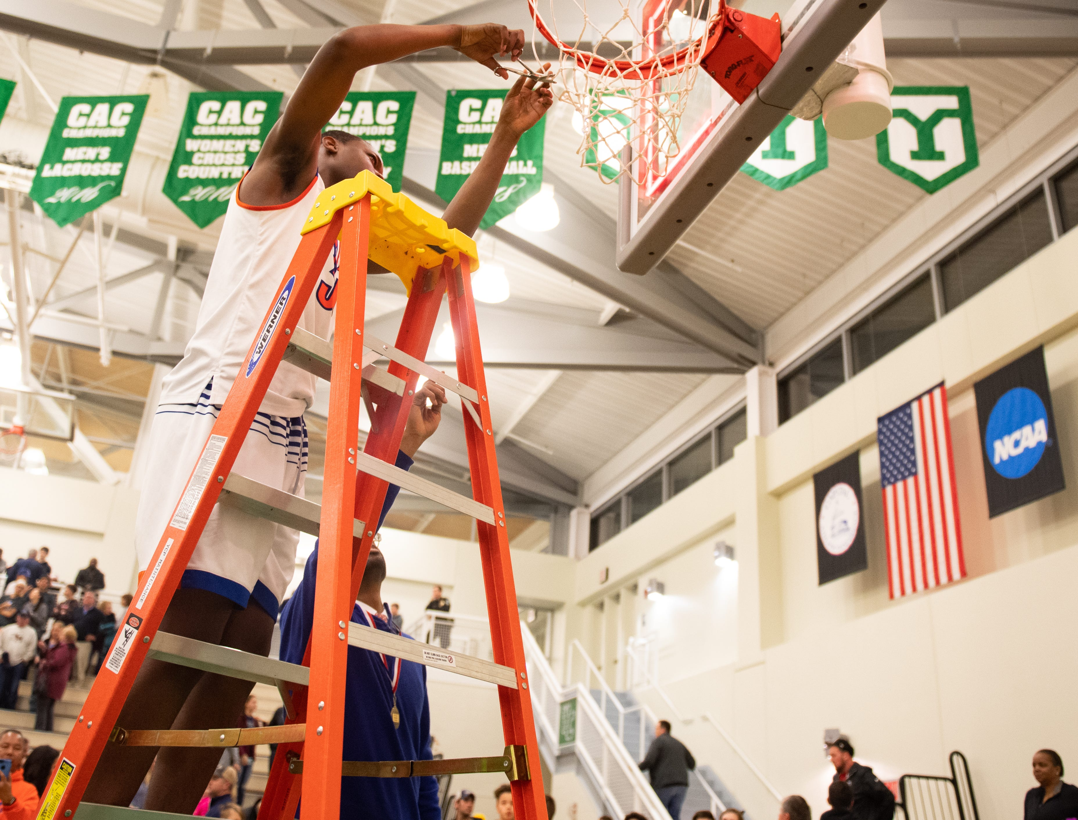 Tamir Beard (34) is the first one to cut off a piece of the net after the YAIAA Division I title game between York High and New Oxford, Friday, February 15, 2019 at York College. The Bearcats defeated the Colonials 54 to 50.