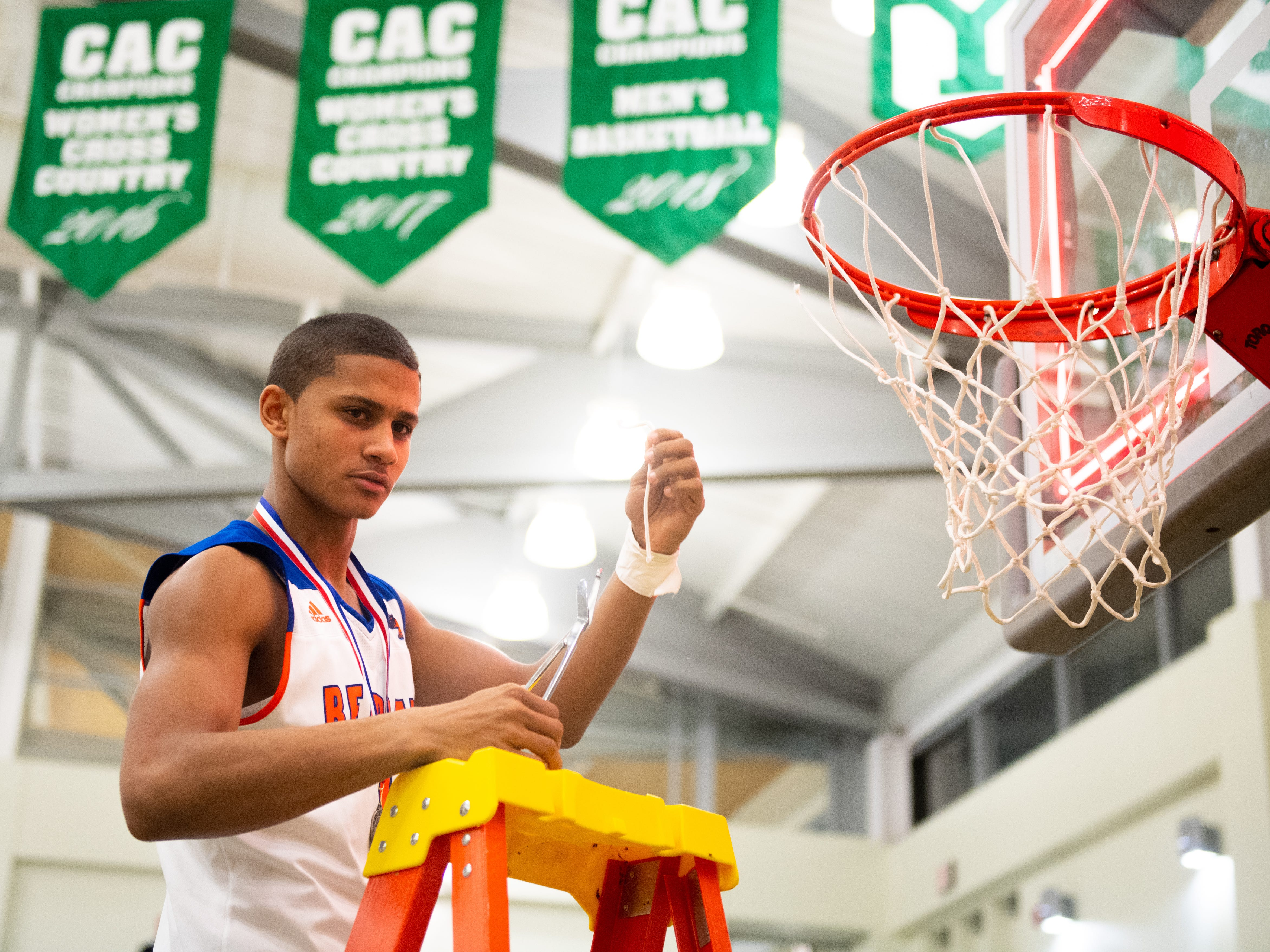 Tobee Stokes (1) poses with a piece of net that he cut off after the YAIAA Division I title game between York High and New Oxford, Friday, February 15, 2019 at York College. The Bearcats defeated the Colonials 54 to 50.