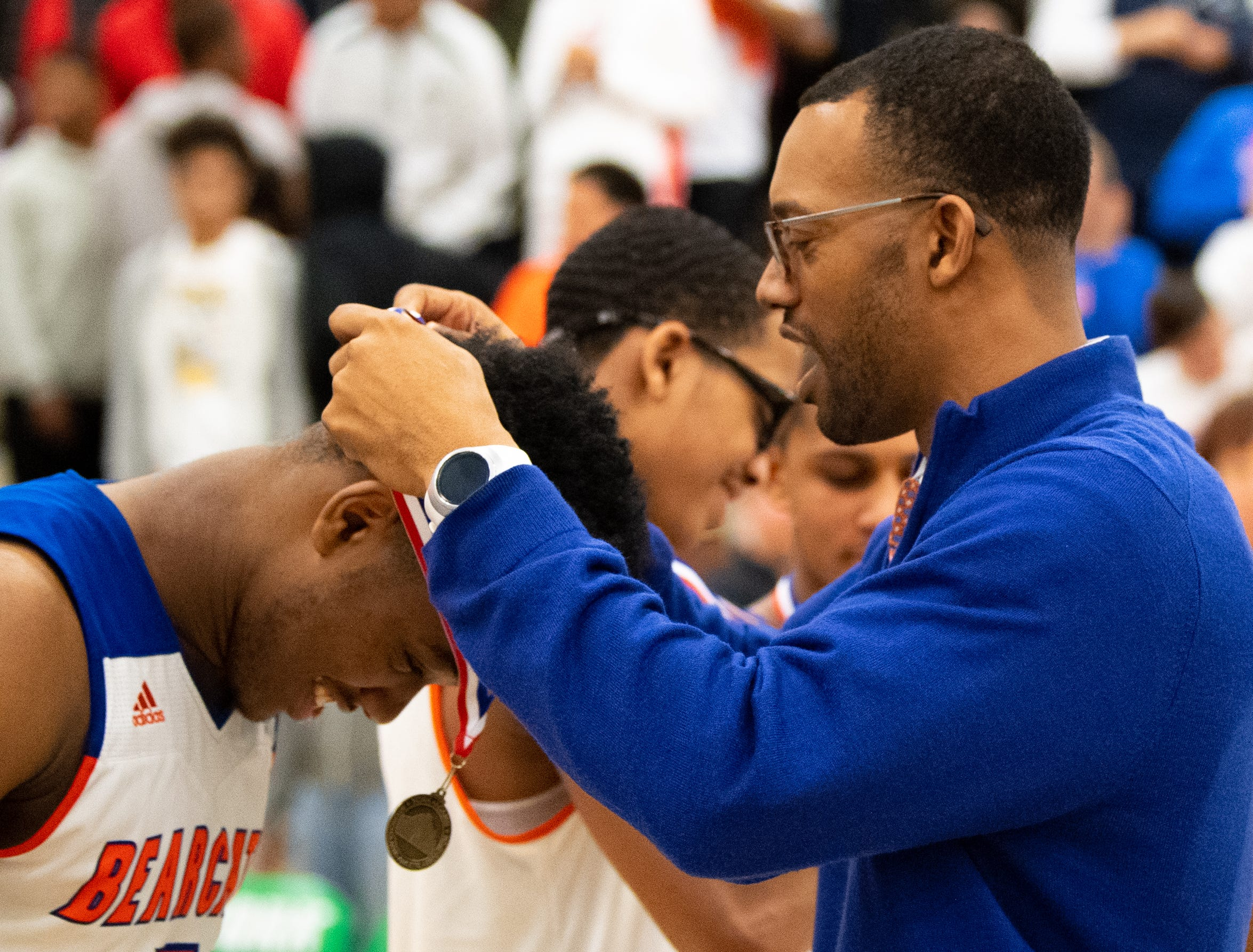 York High head coach Clovis Gallon Sr. presents medals to his team after the YAIAA Division I title game between York High and New Oxford, Friday, February 15, 2019 at York College. The Bearcats defeated the Colonials 54 to 50.