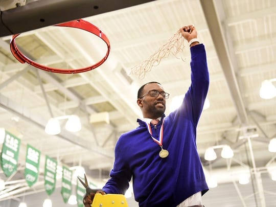 York High boys' basketball coach Clovis Gallon raises the net above his head after his team's 54-50 victory over New Oxford in the YAIAA title game at York College Friday.