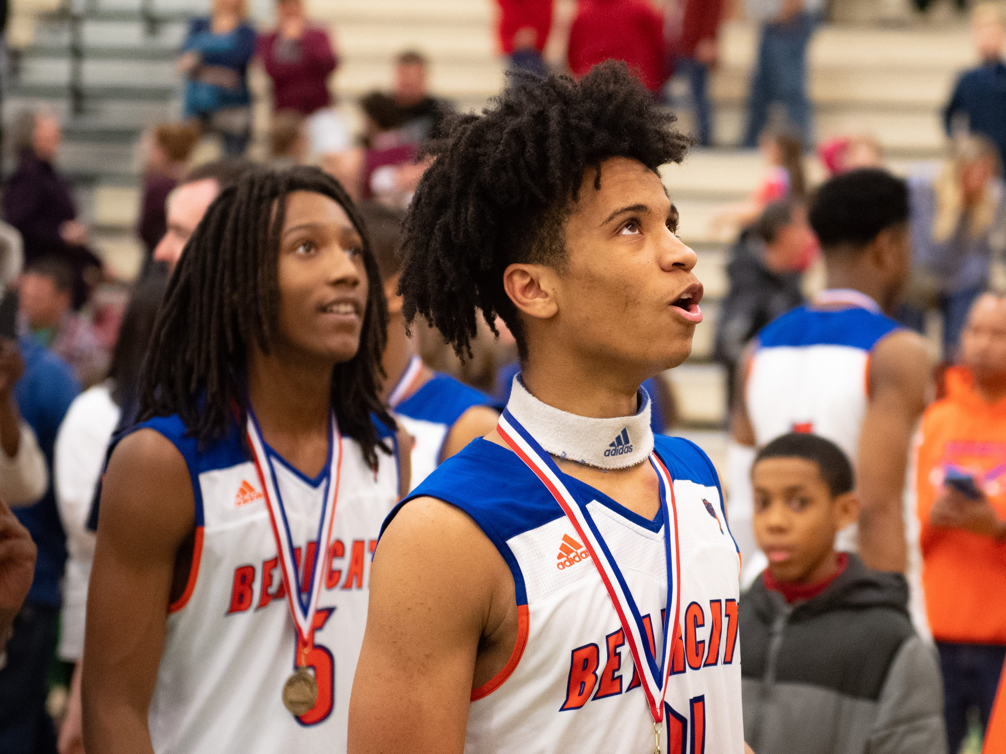 Edward Minter (5) and Jaevon Woodyard (4) watch as their team cuts down the net after the YAIAA Division I title game between York High and New Oxford, Friday, February 15, 2019 at York College. The Bearcats defeated the Colonials 54 to 50.
