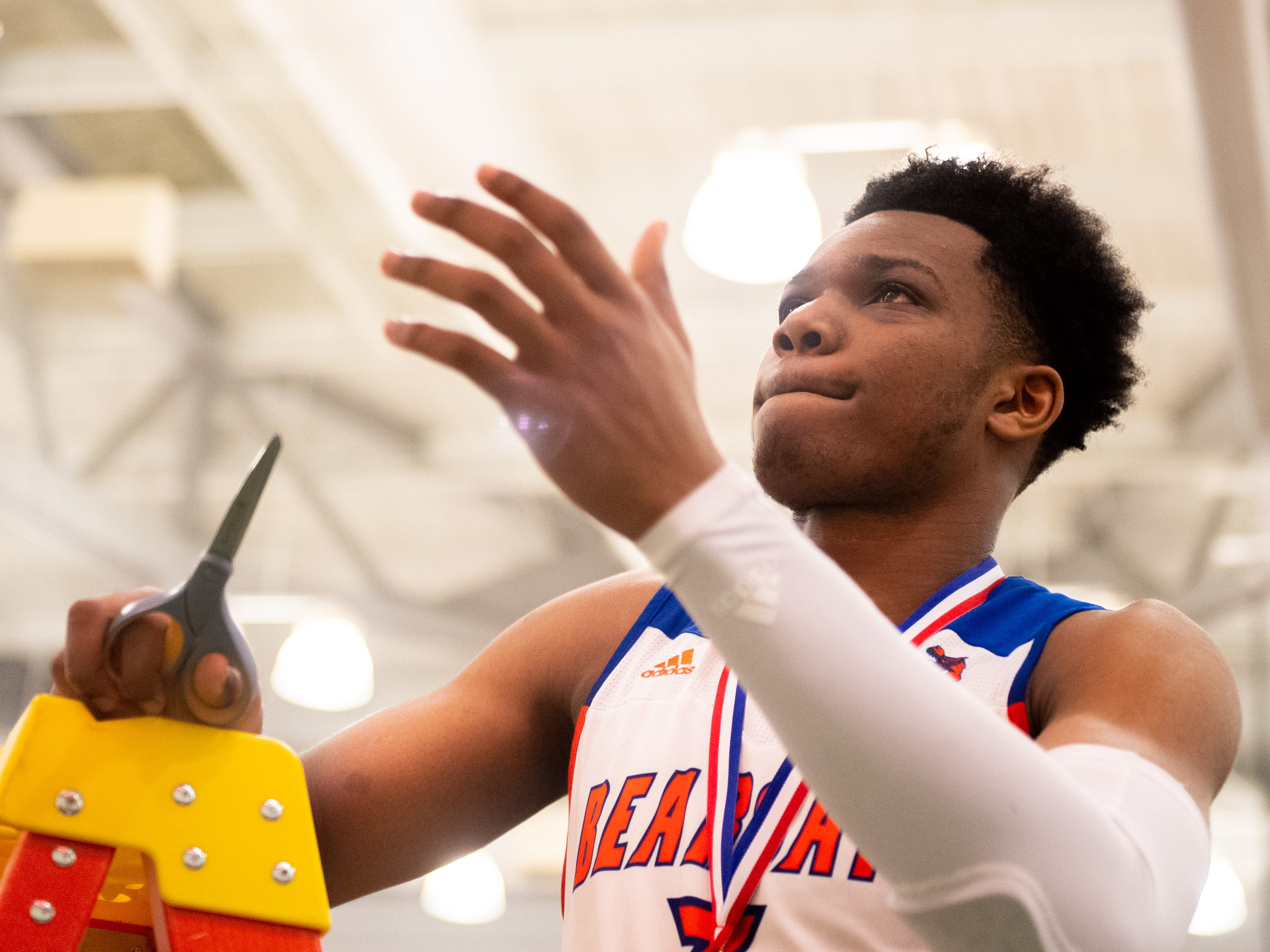 Clovis Gallon Jr. (3) picks a part of the net to take after the YAIAA Division I title game between York High and New Oxford, Friday, February 15, 2019 at York College. The Bearcats defeated the Colonials 54 to 50.