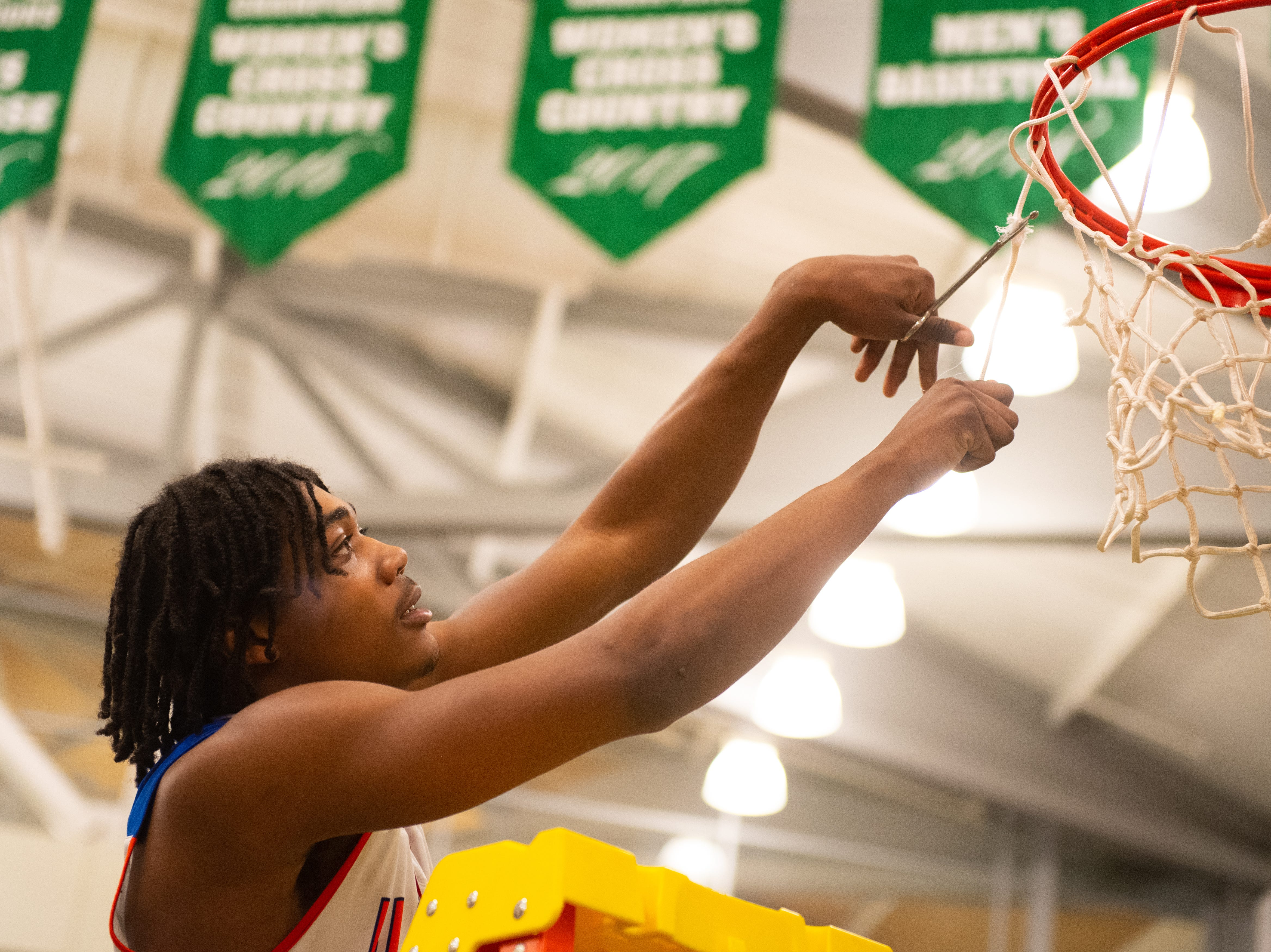 Branden Mutunga (11) takes a piece of the net after the YAIAA Division I title game between York High and New Oxford, Friday, February 15, 2019 at York College. The Bearcats defeated the Colonials 54 to 50.
