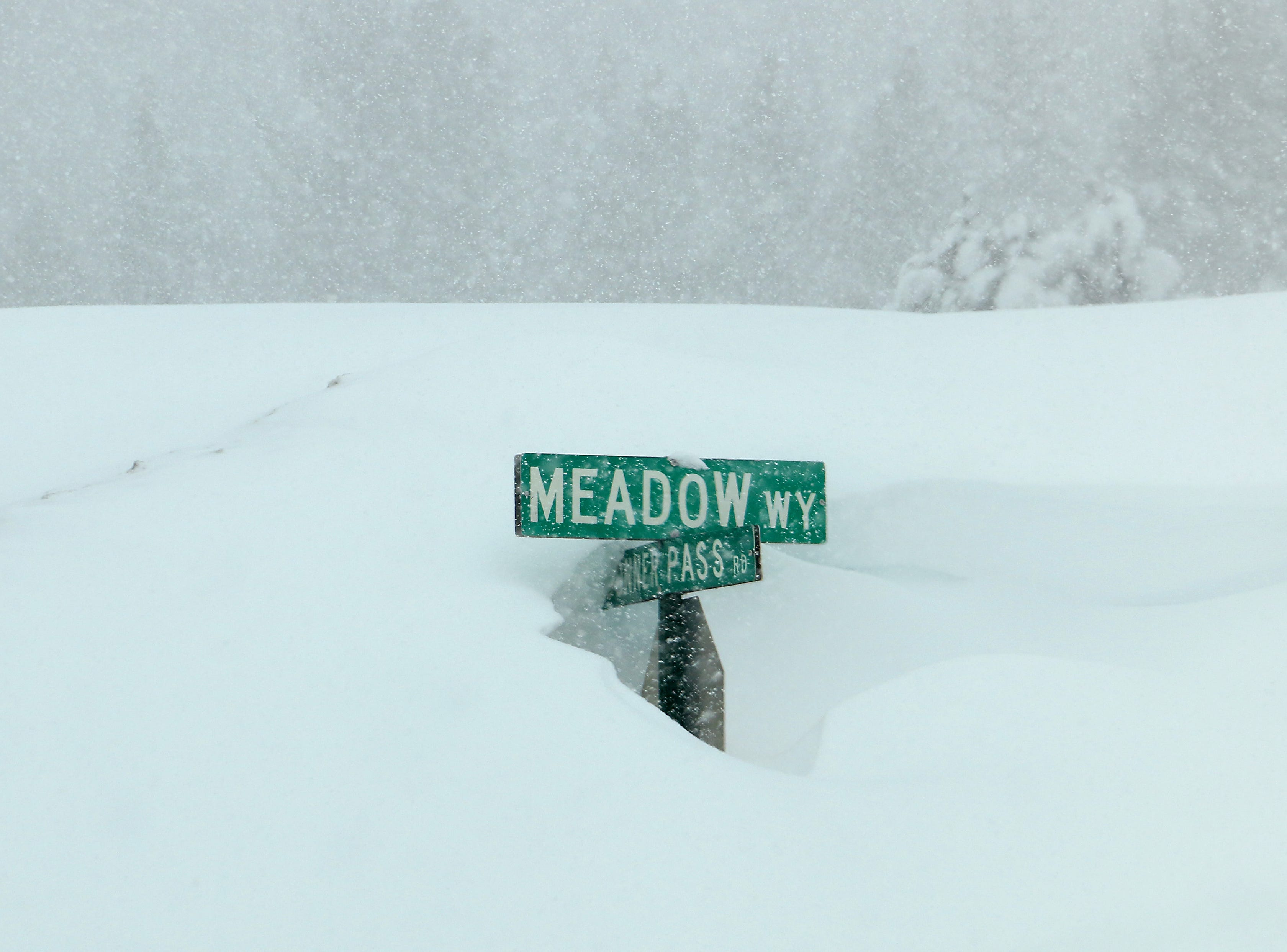 A street sign is seen mostly buried in Truckee, Calif. on Feb. 16, 2019.
