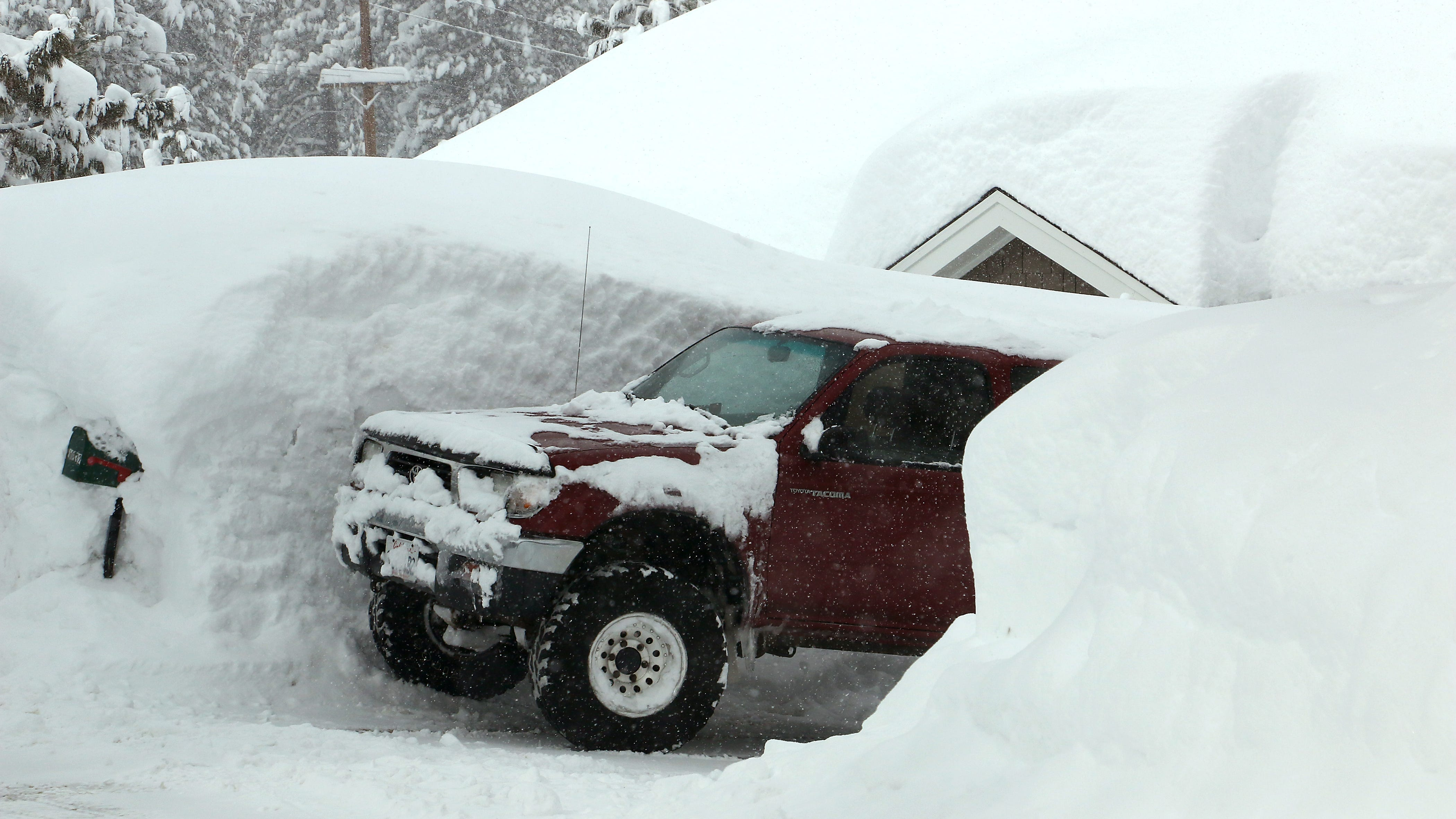 A truck peaks out from its snowy parking spot in...