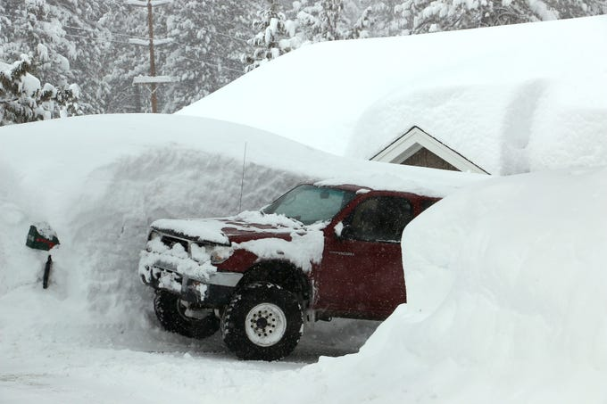 A truck peaks out from its snowy parking spot in Truckee, Calif. on Feb. 16, 2019.