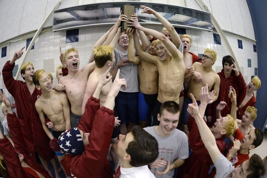 Canandaigua swimmers hoist the championship block after winning the Section V Class B Swimming & Diving Championships at the Webster Aquatic Center, Friday, Feb. 15, 2019.