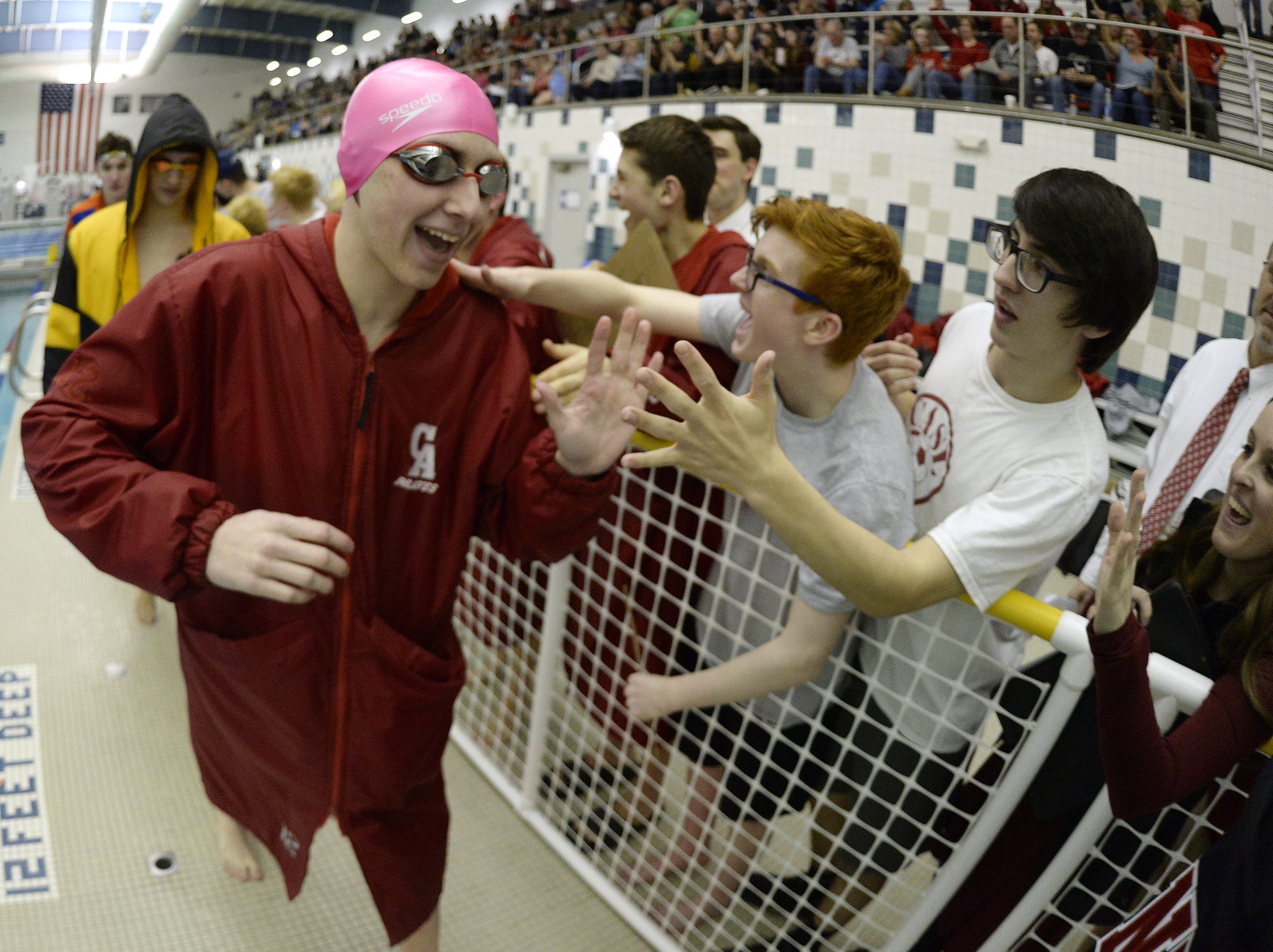 Canandaigua's Hayden Bement is cheered on by teammates on his way to swim in the final of the 100 yard freestyle during the Section V Class B Swimming & Diving Championships at the Webster Aquatic Center, Friday, Feb. 15, 2019.