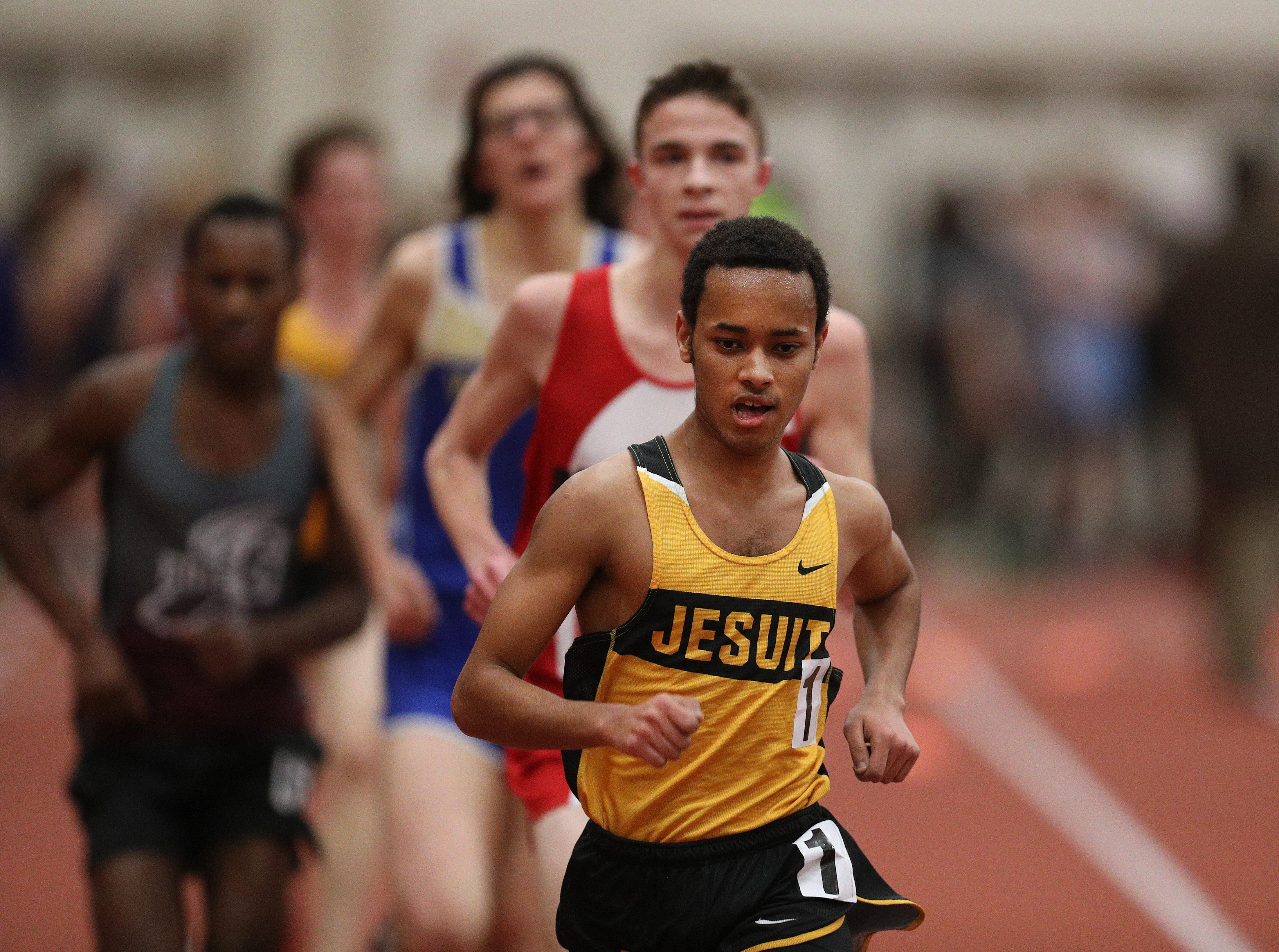 McQuaid's Able Hagos moves to the front of the pack to win the Class A 3200 meter run.