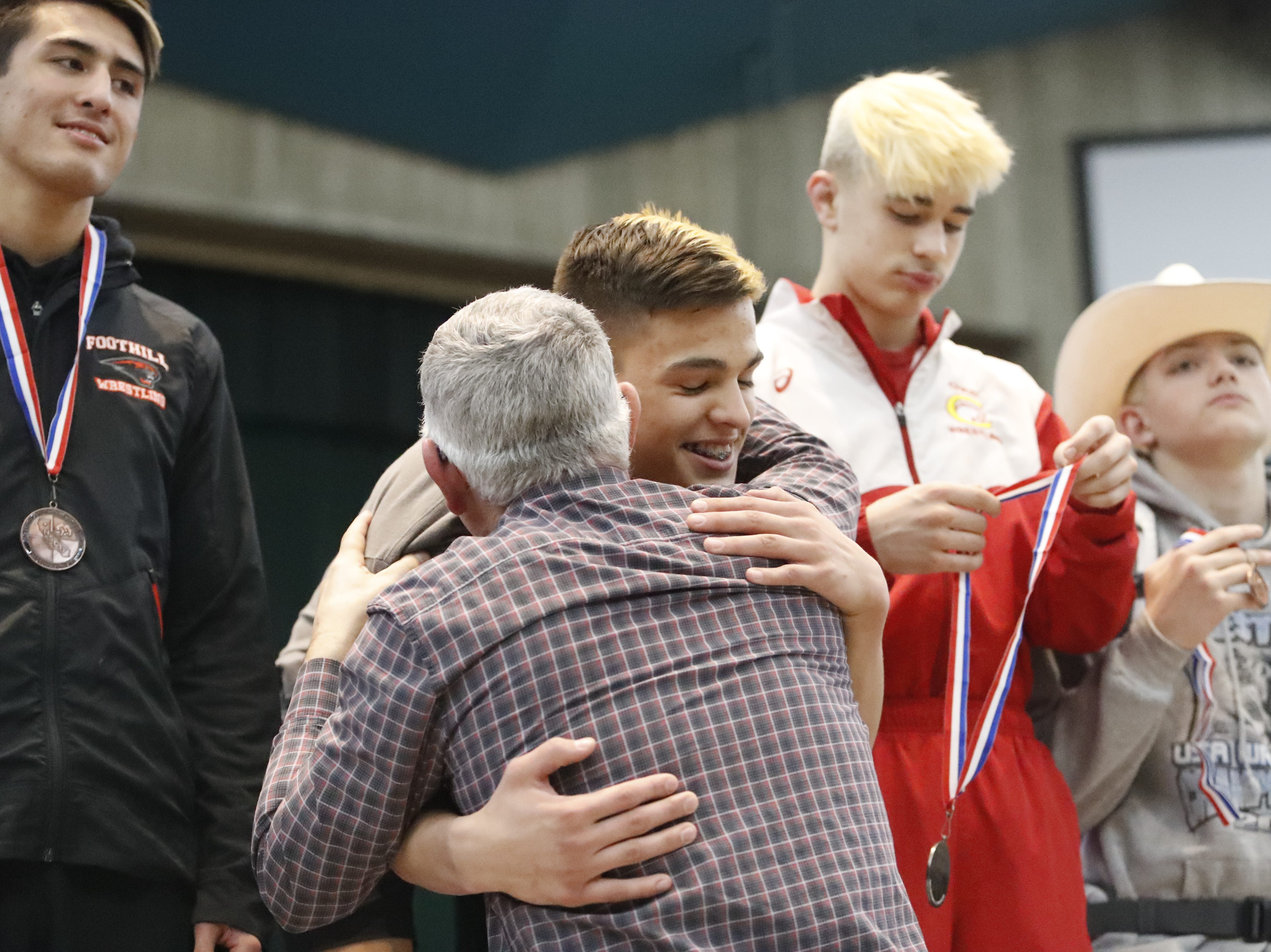 West Valley wrestler Rocky Raby hugs his coach from the podium after winning the 132-pound Northern Section championship on Friday, Feb. 15, at the Redding Civic Auditorium.