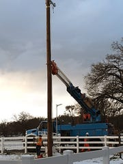 A Pacific Gas & Electric crew sets a pole in Shasta County following this week's snowstorm.