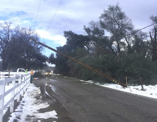 A utility crew assesses a broken power pole in Shasta County following this week's snowstorm.