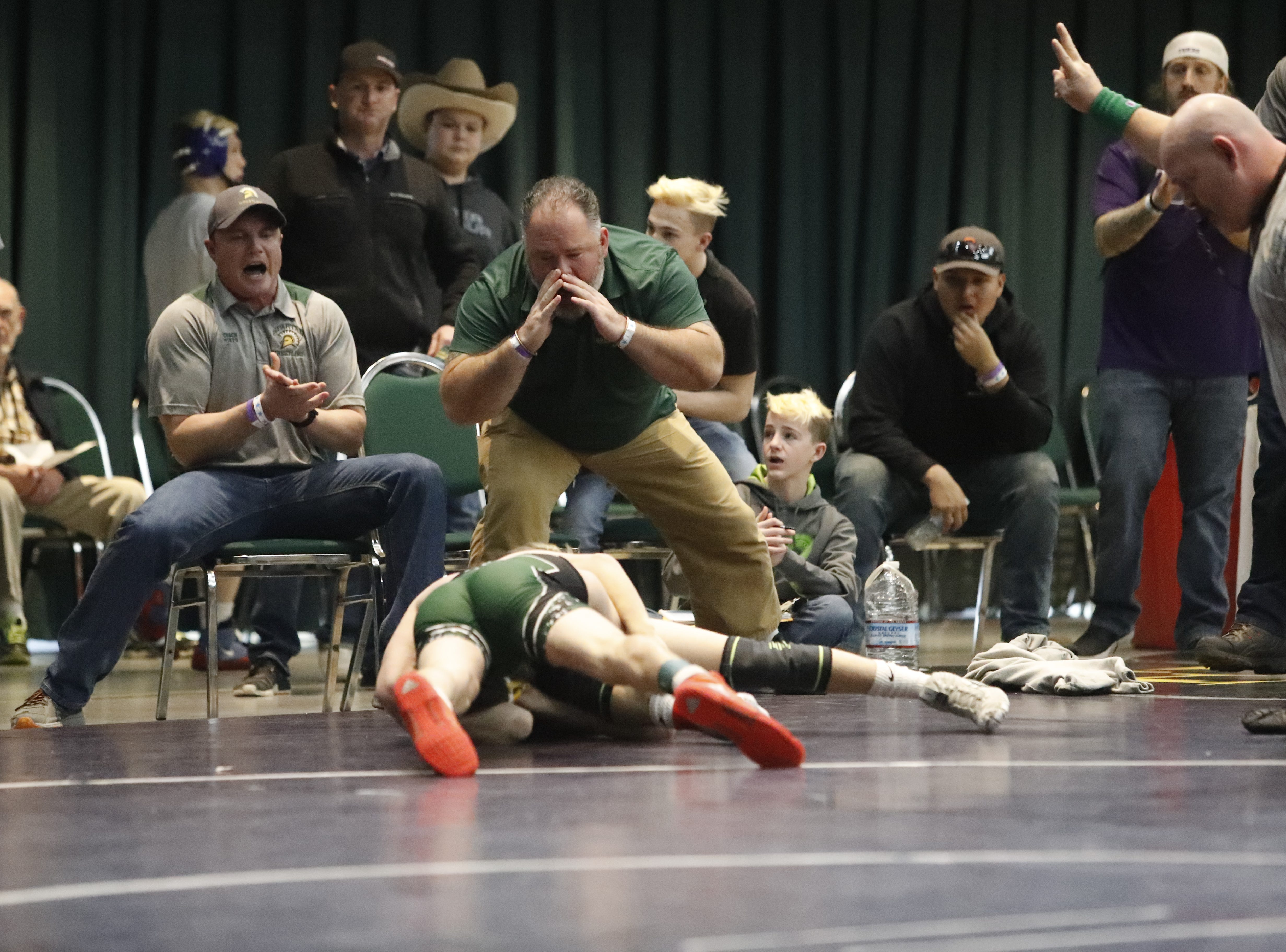 Red Bluff coaches shout directions to 113-pound wrestler AJ Strole at the Northern Section championships on Friday, Feb. 15, at the Redding Civic Auditorium.